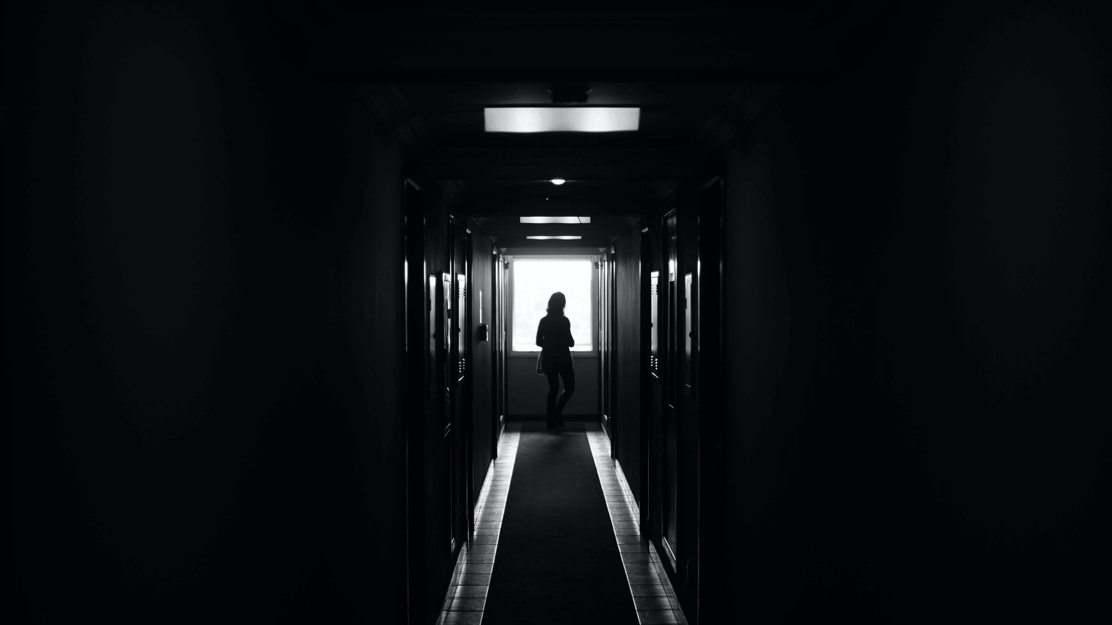 Person Standing on Dark Hallway