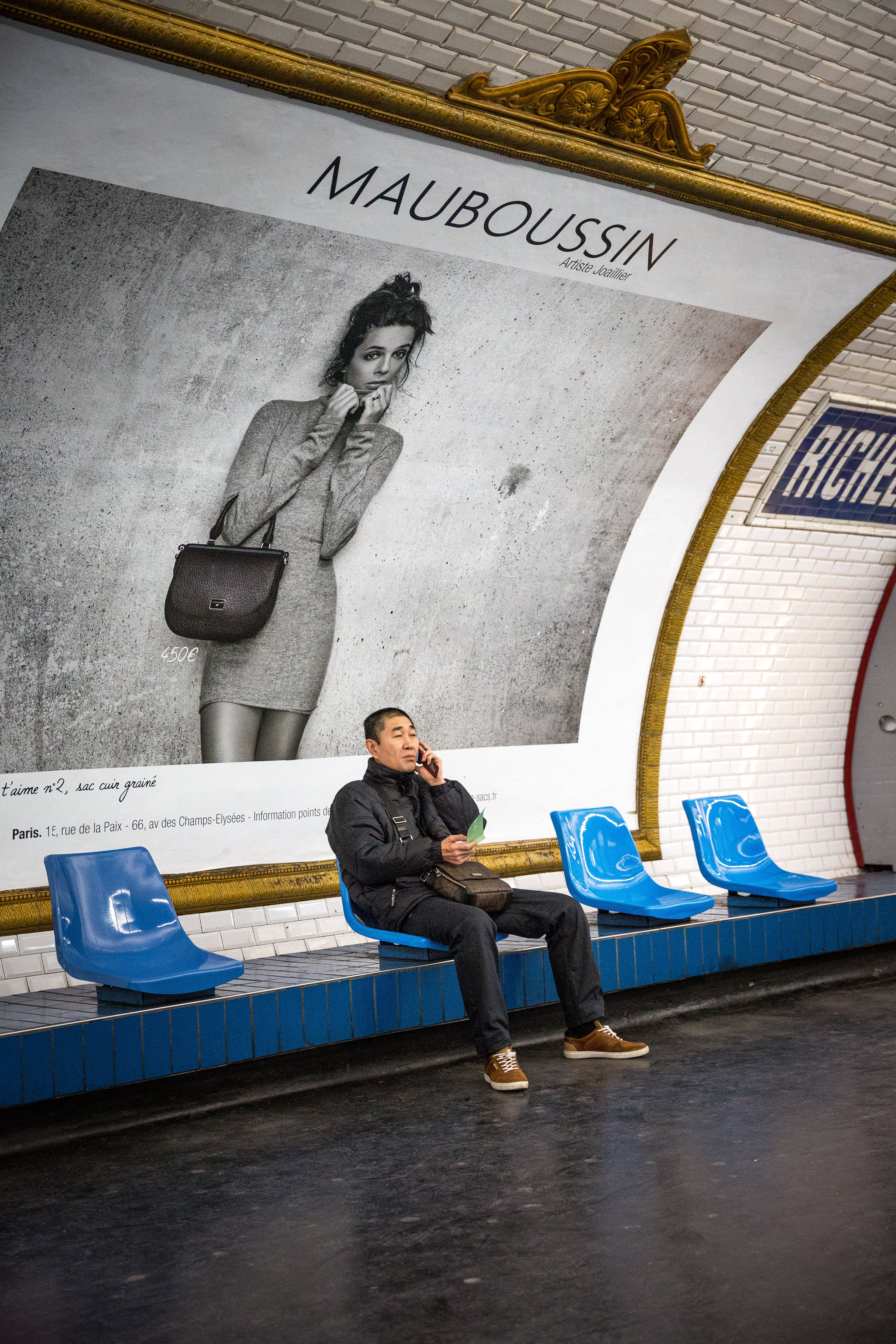 Man Sitting on Blue Chair in Front of Mauboussin Signage