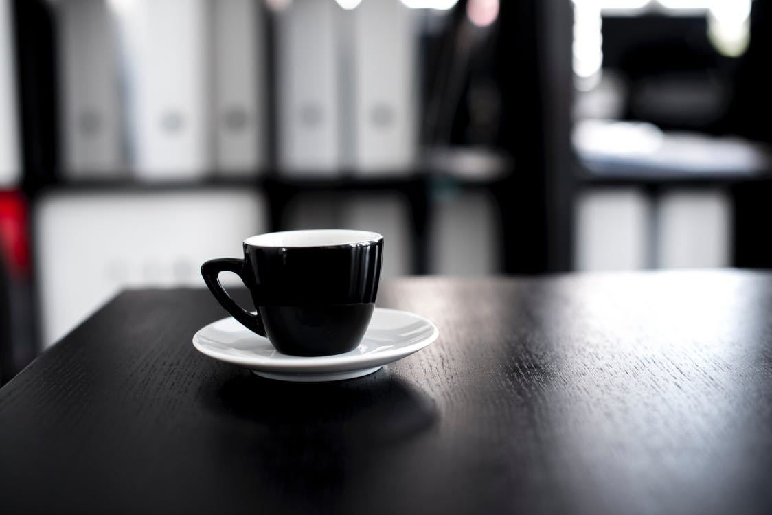 Black and White Ceramic Tea Cup With Saucer on Black Wooden Table