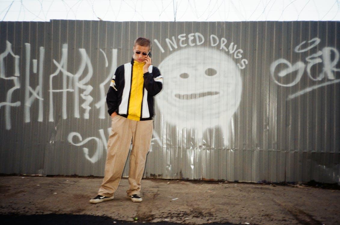 Man Standing Near Wall Holding Phone