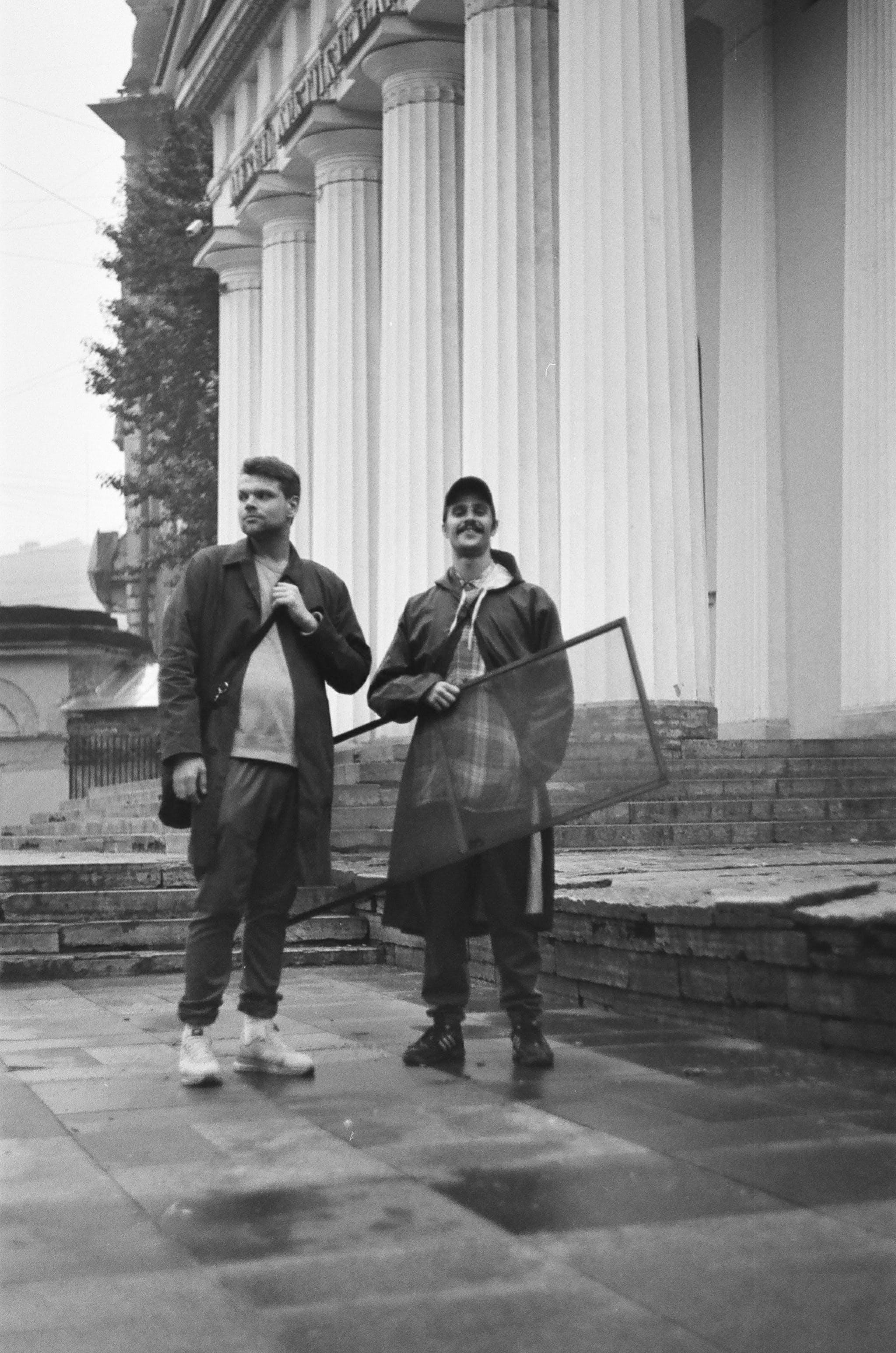 Greyscale Photo of Two Men Standing on Floor