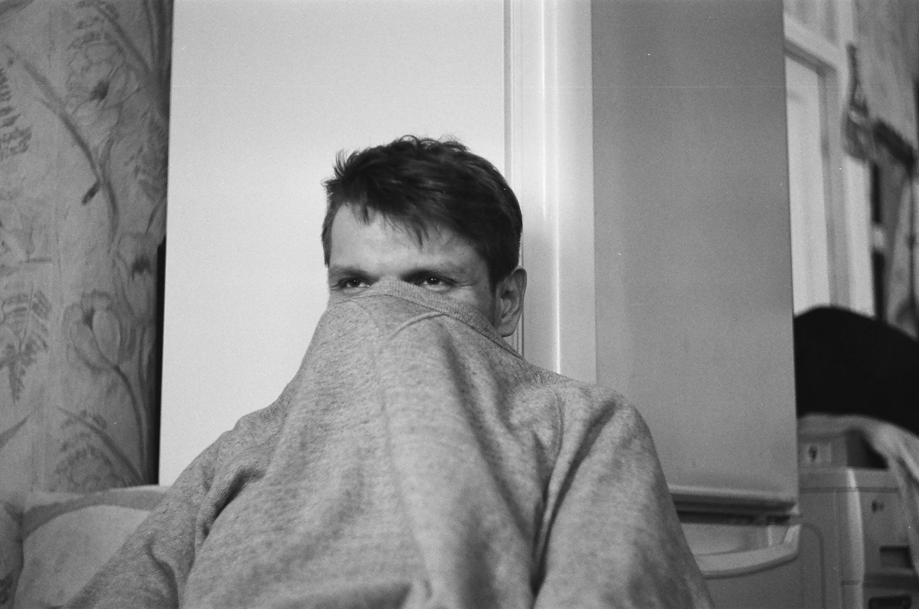 Grayscale Photo of Man Leaning on Refrigerator
