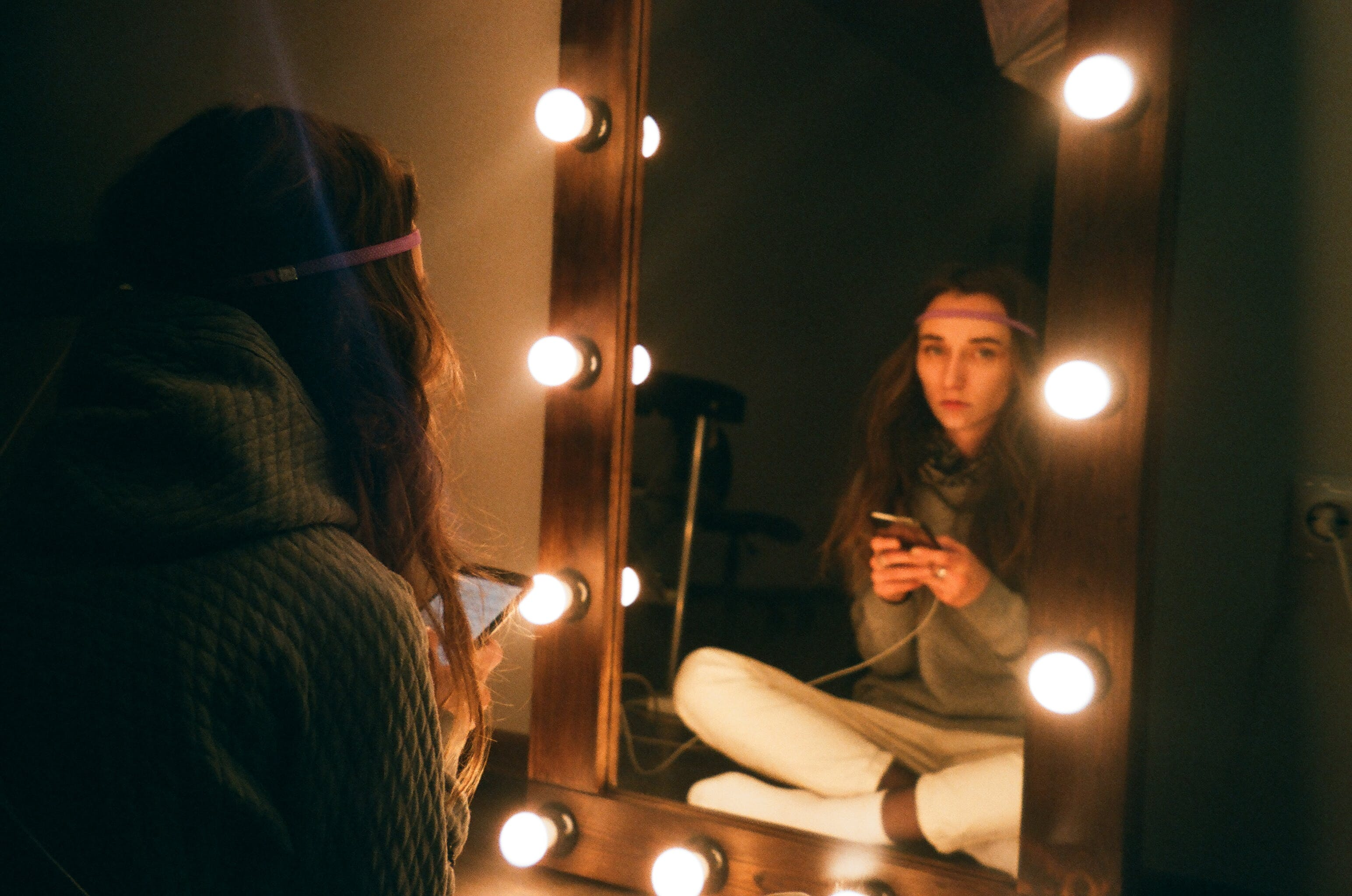 Woman Sitting in Front of Vanity Mirror
