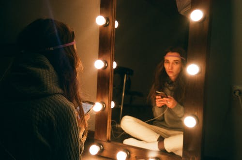 Woman Sitting in Front of Vanity Mirror