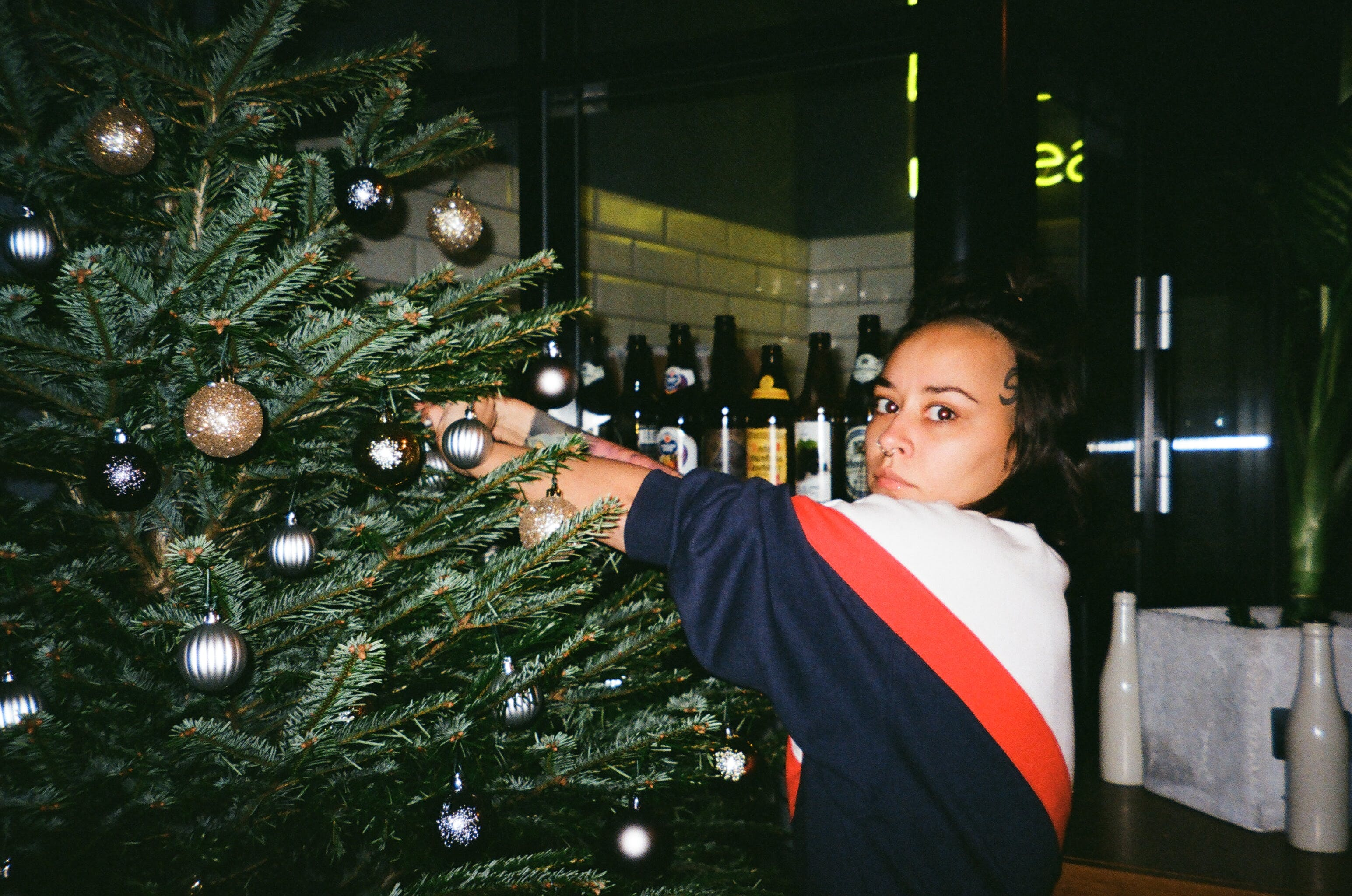 Woman Wearing Sweater Holding Christmas Tree With Baubles Inside the Room