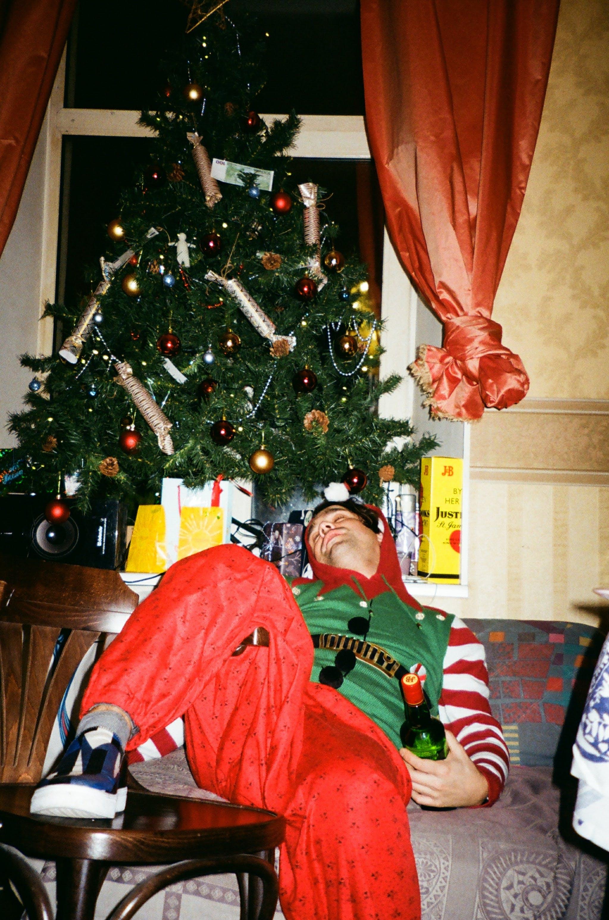 Man Lying Beside Green Christmas Tree