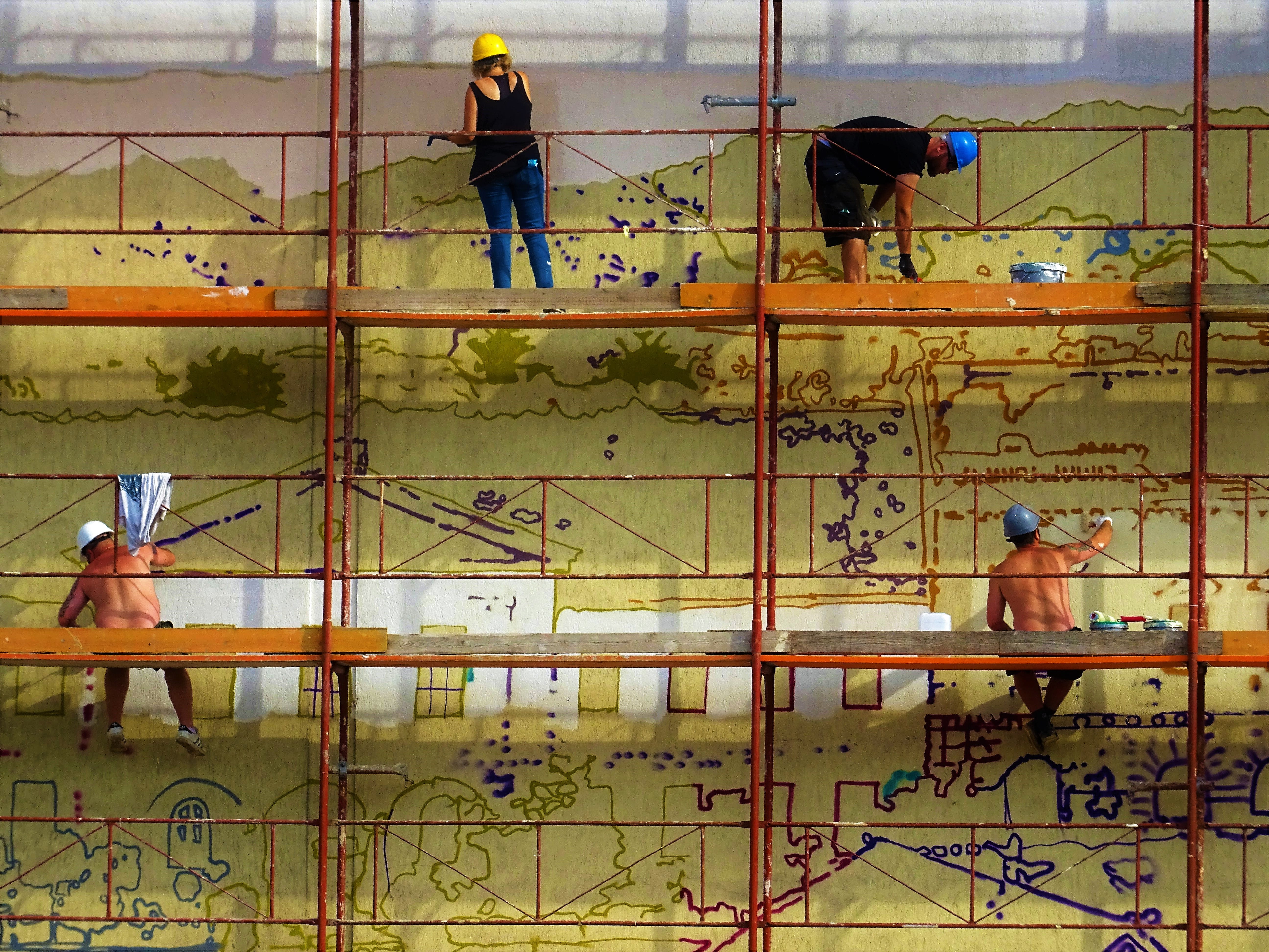 Four People Painting Wall on Scaffolding