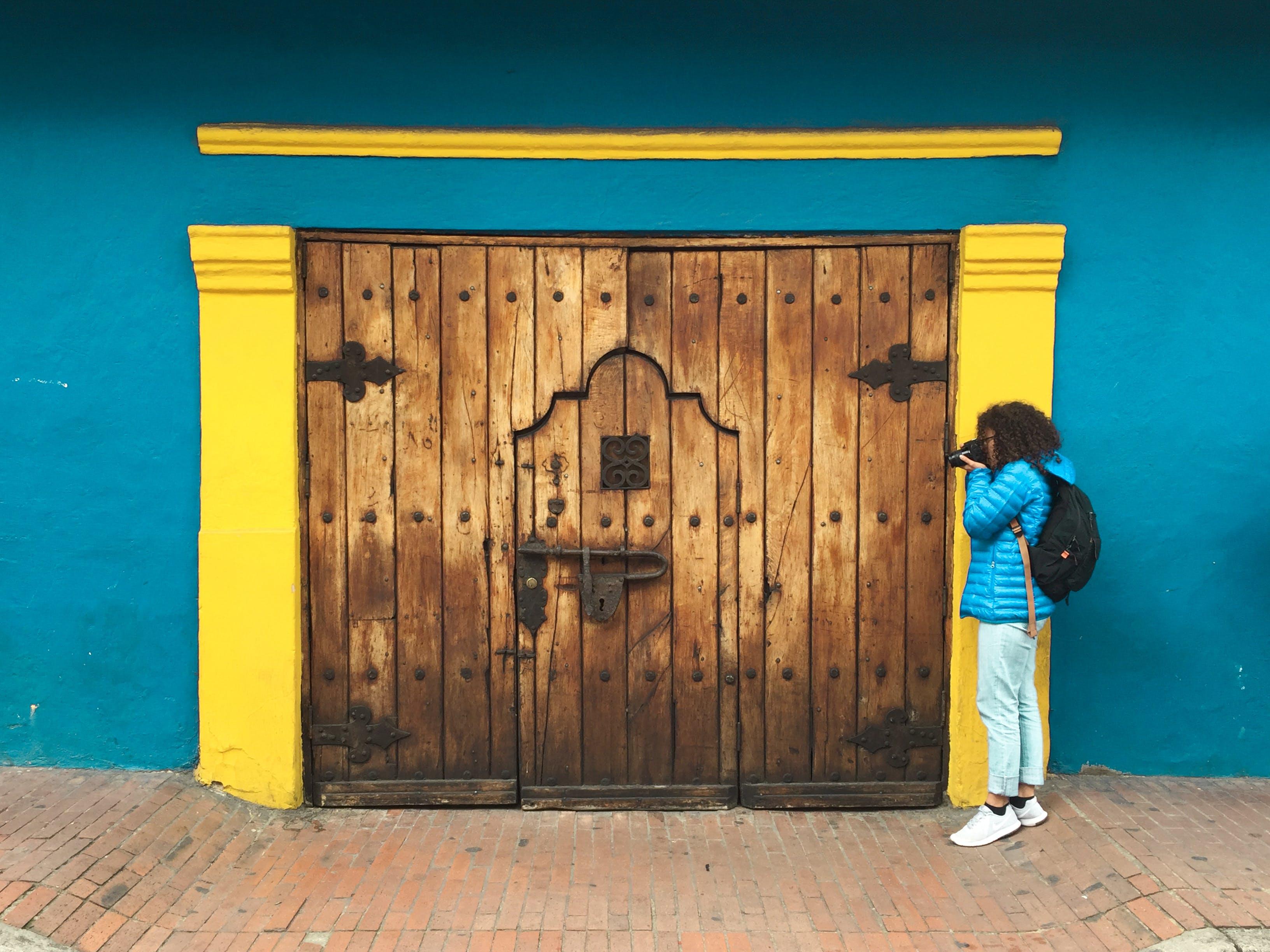 Person Taking Photo of Brown Wooden Door