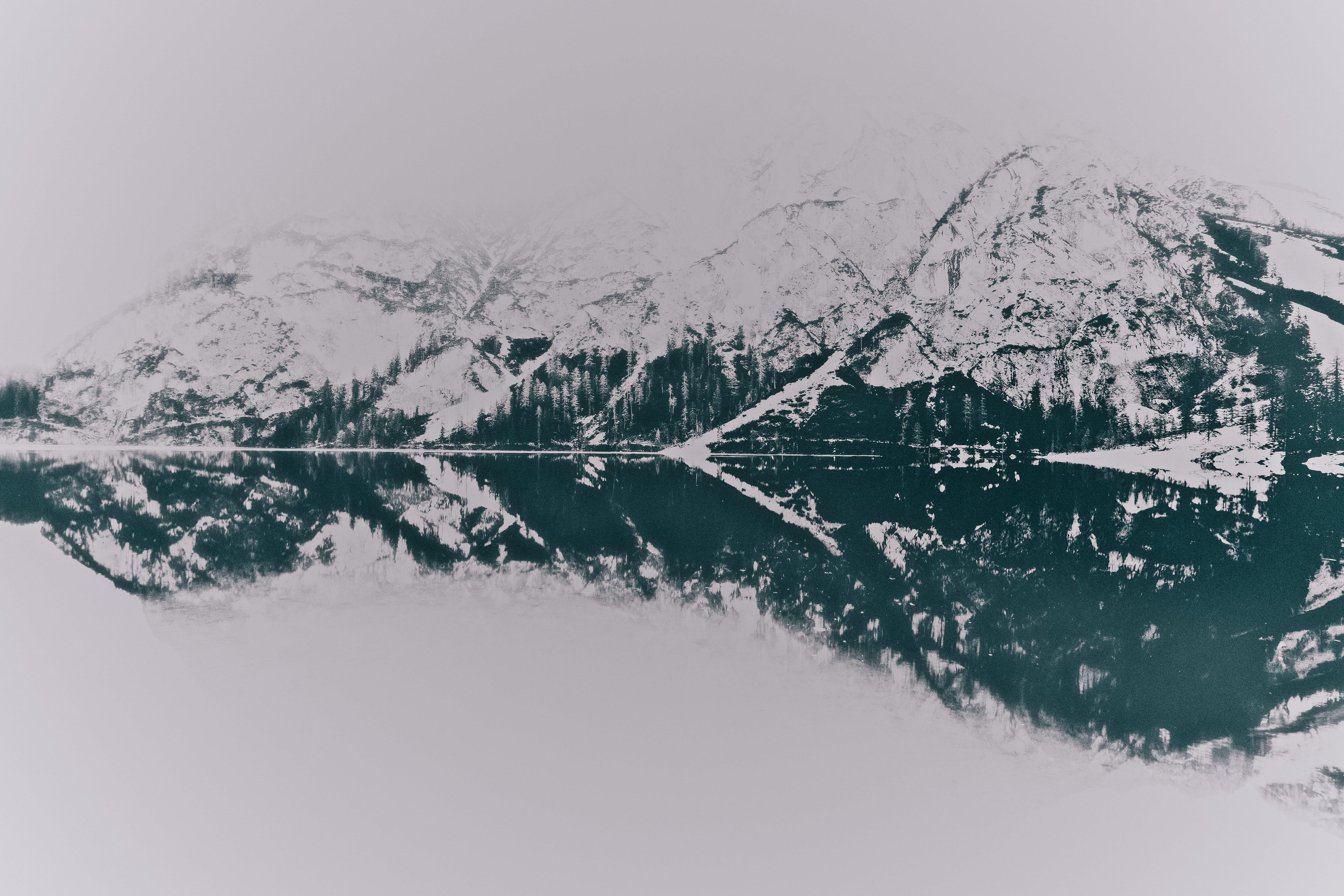 Landscape Photo of Snowy Mountains Near Lake