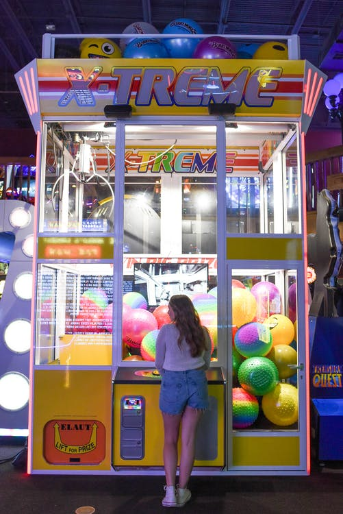 Woman Standing in Front of X-treme Arcade Machine