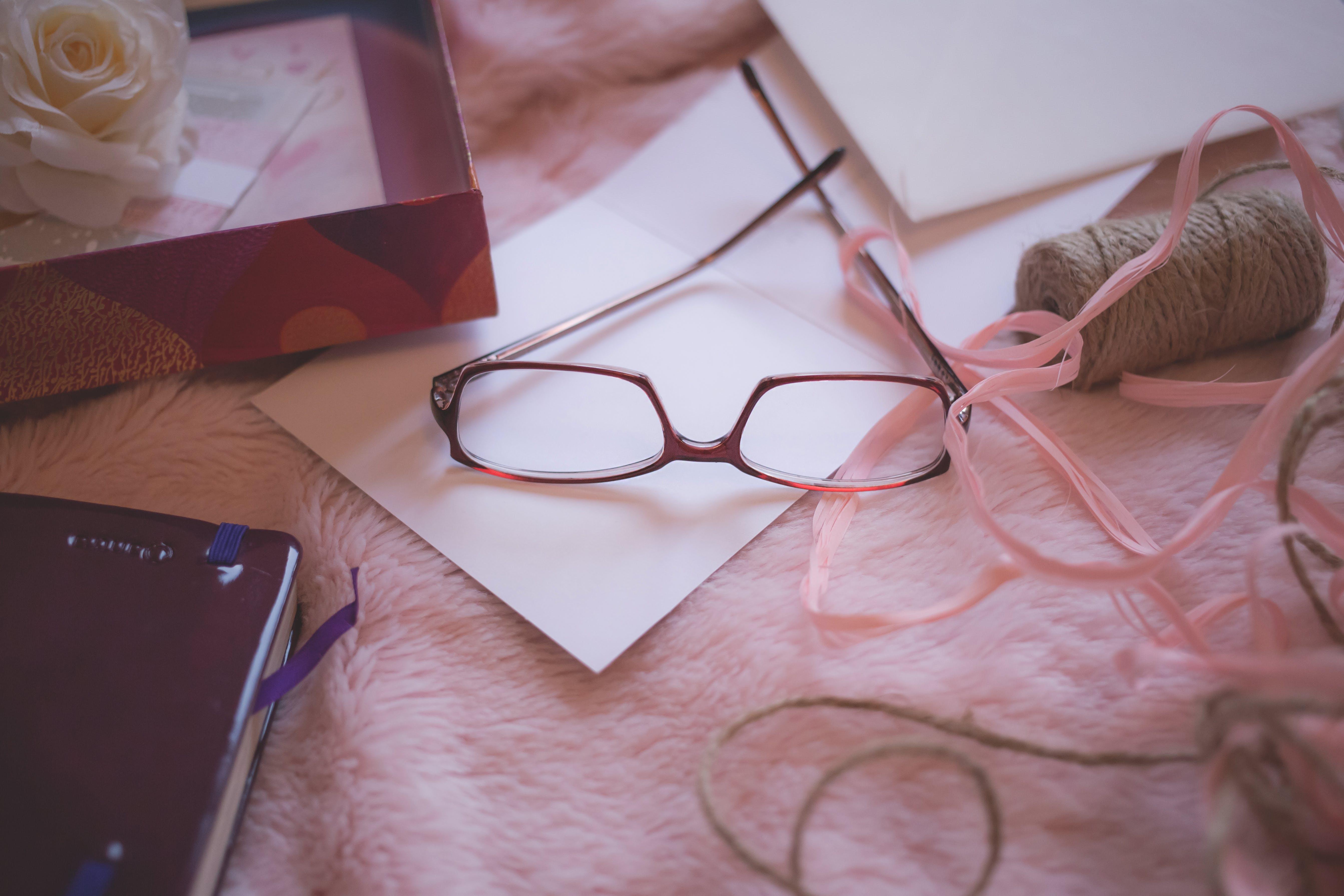 Eyeglasses Beside Pink Yarn on Pink Bed Blanket