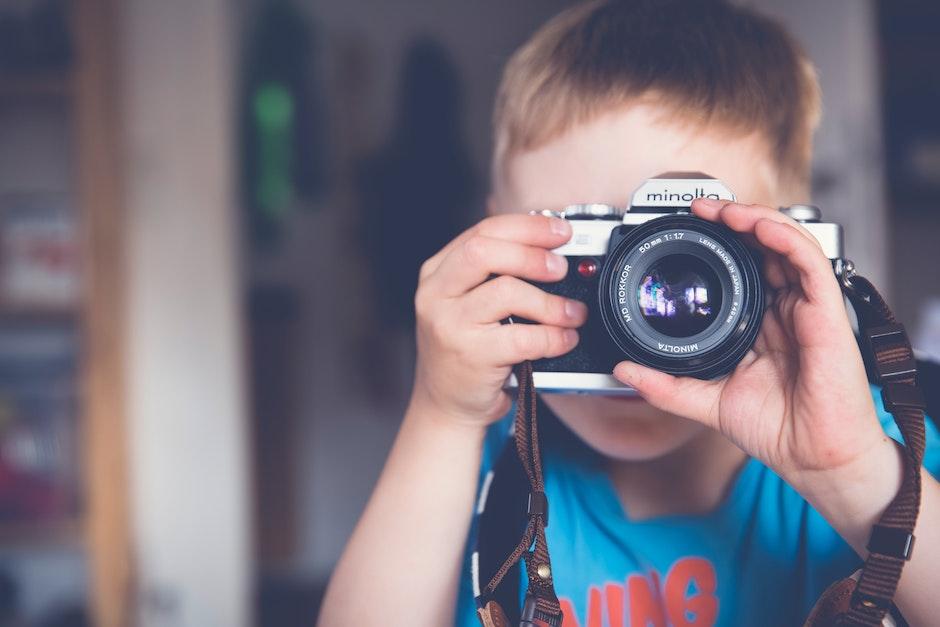 Boy in Blue Crew Neck T Shirt Taking Photo Using Minolta Dslr Camera during Daytime