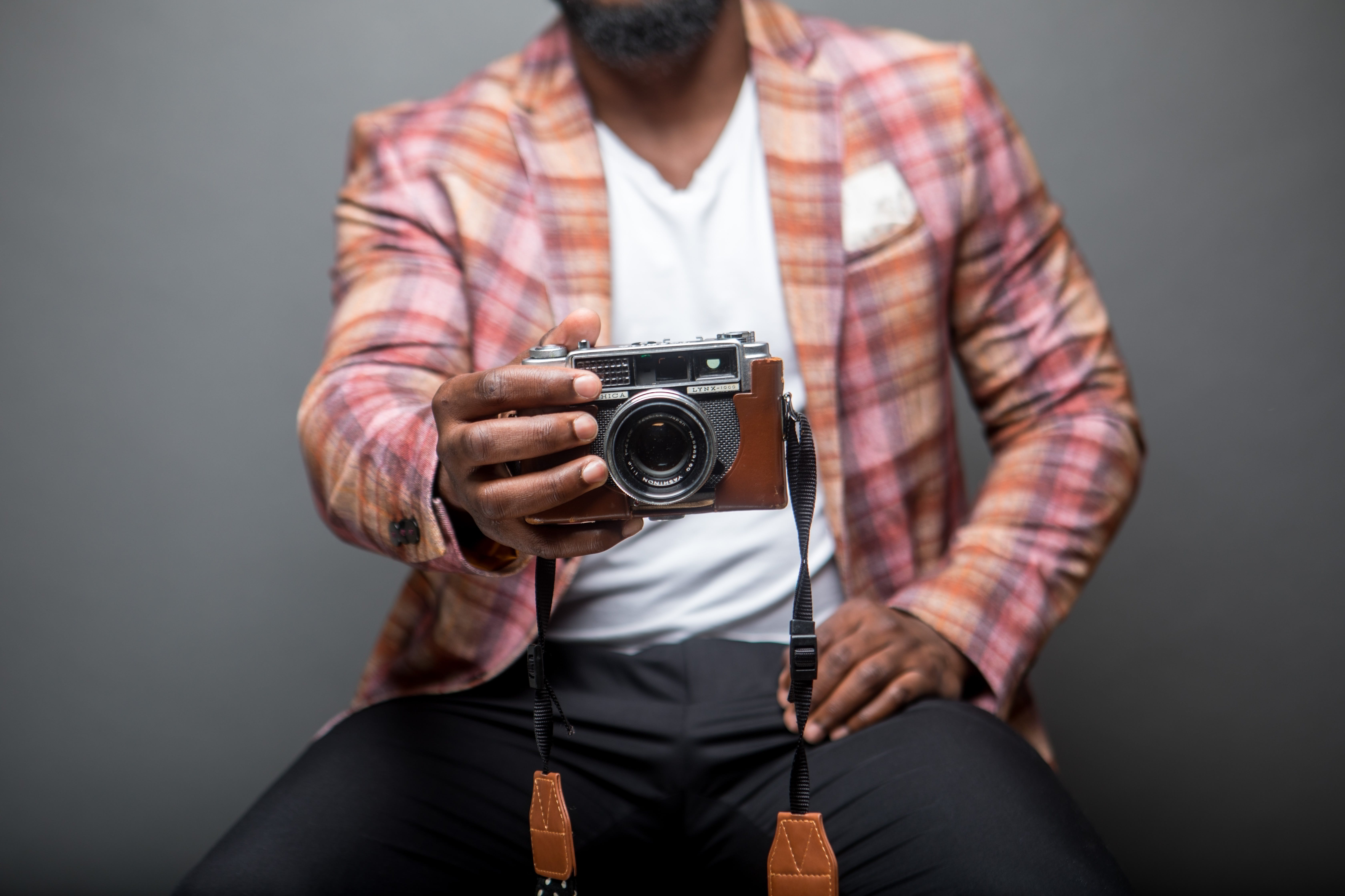 Selective Focus Photography of Man Sits While Holding Camera