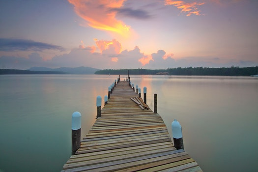 Brown Wooden Footbridge on Body of Water during Sunrise