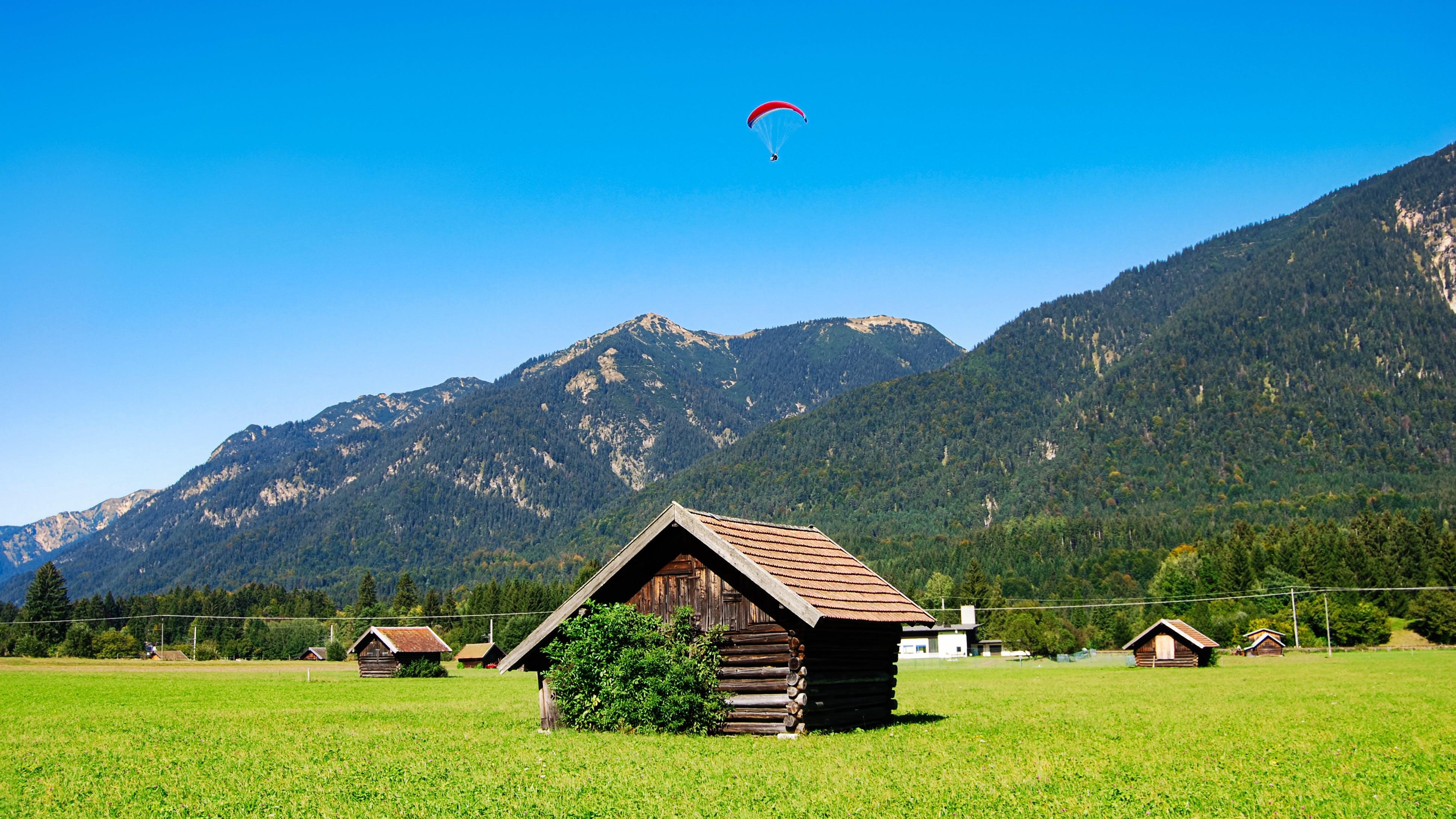 Brown Wooden House on Grass Field Near Mountain