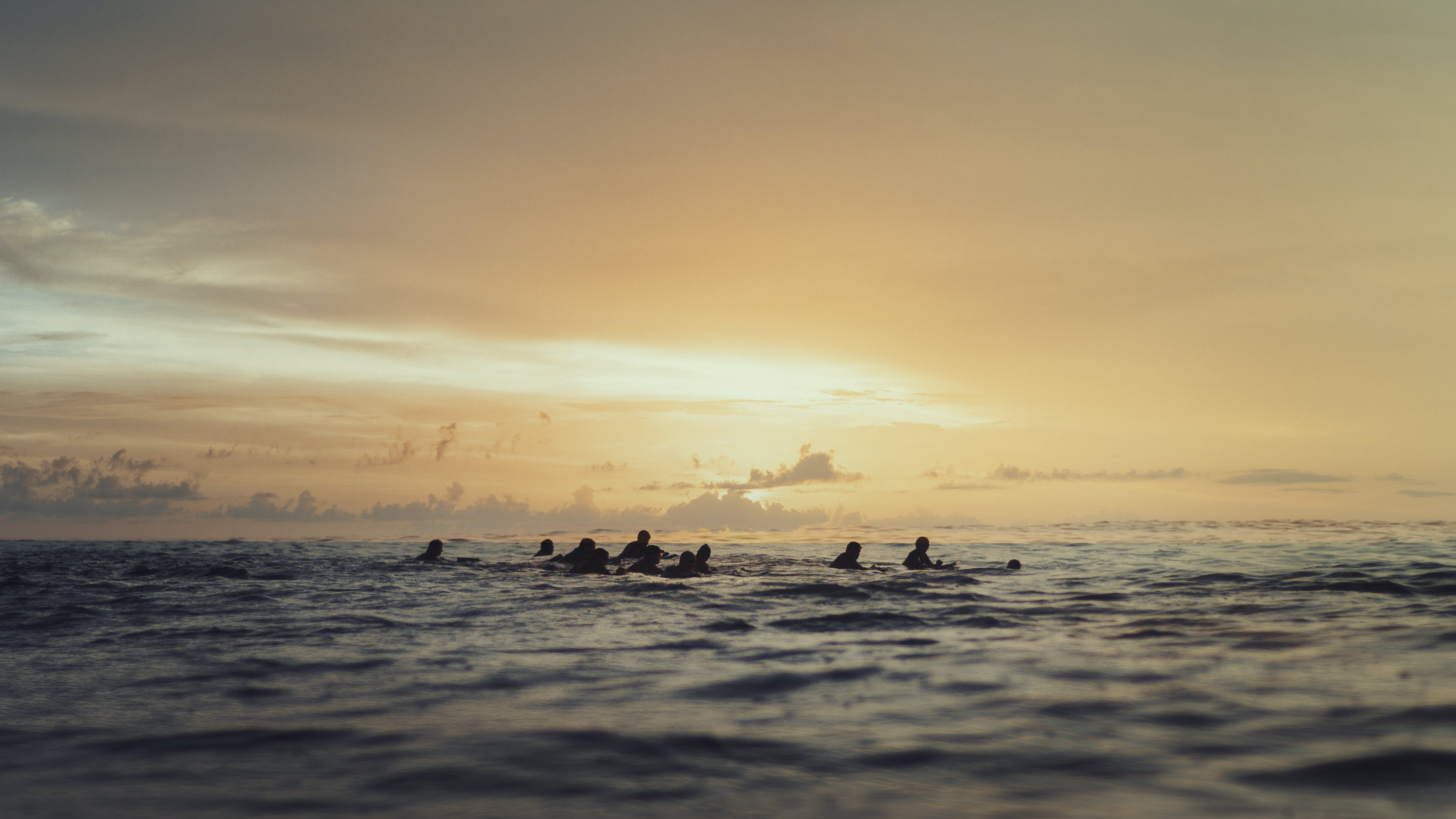 People Swimming on Ocean during Sunset