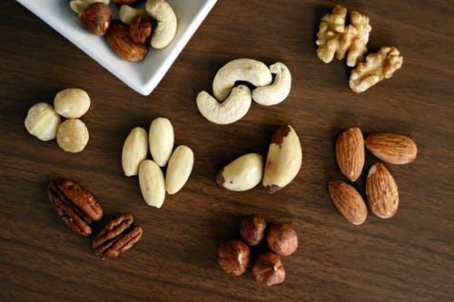 Variety of Brown Nuts on Brown Wooden Panel High-angle Photo