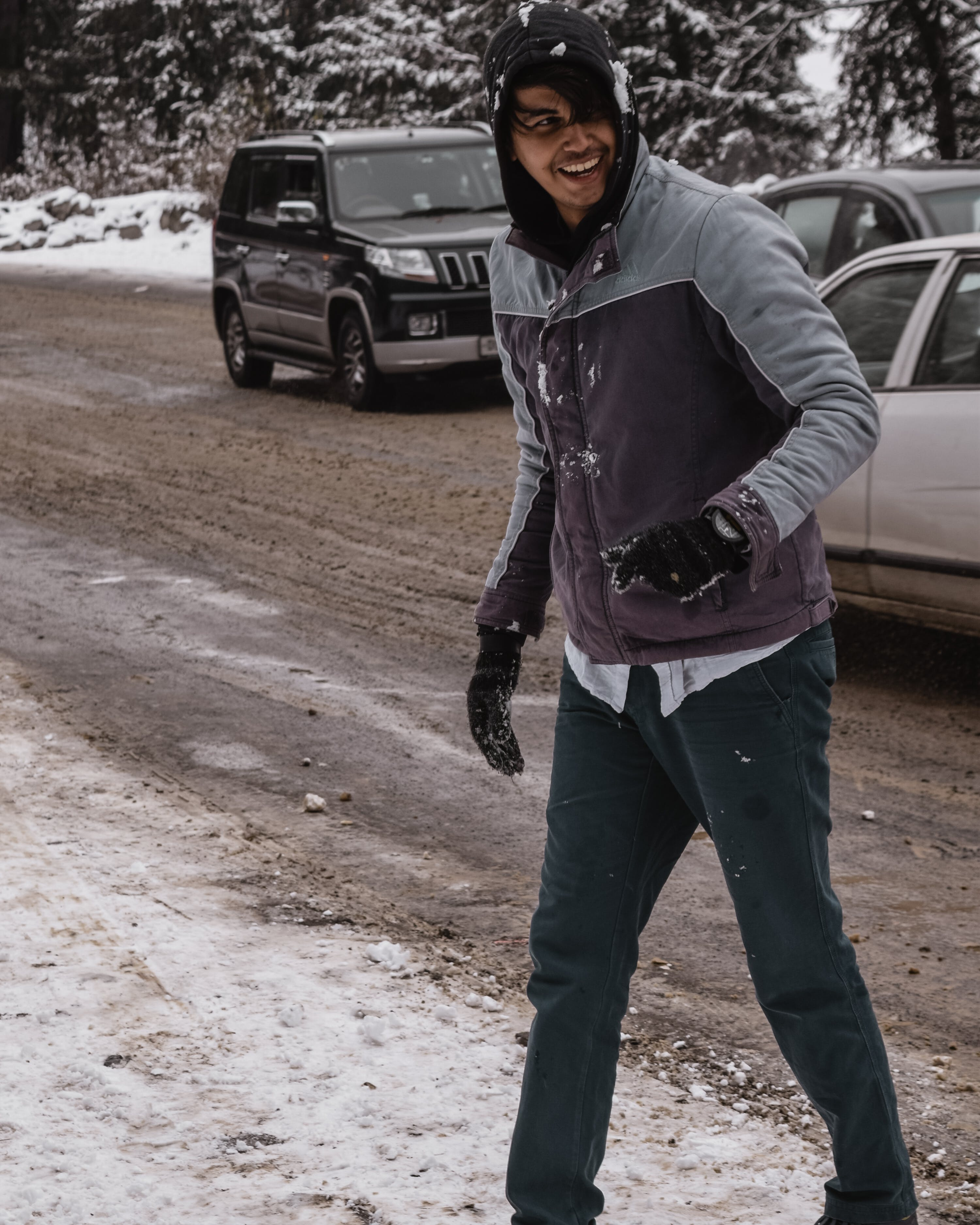 Man in Winter Jacket Laughing Near Cars