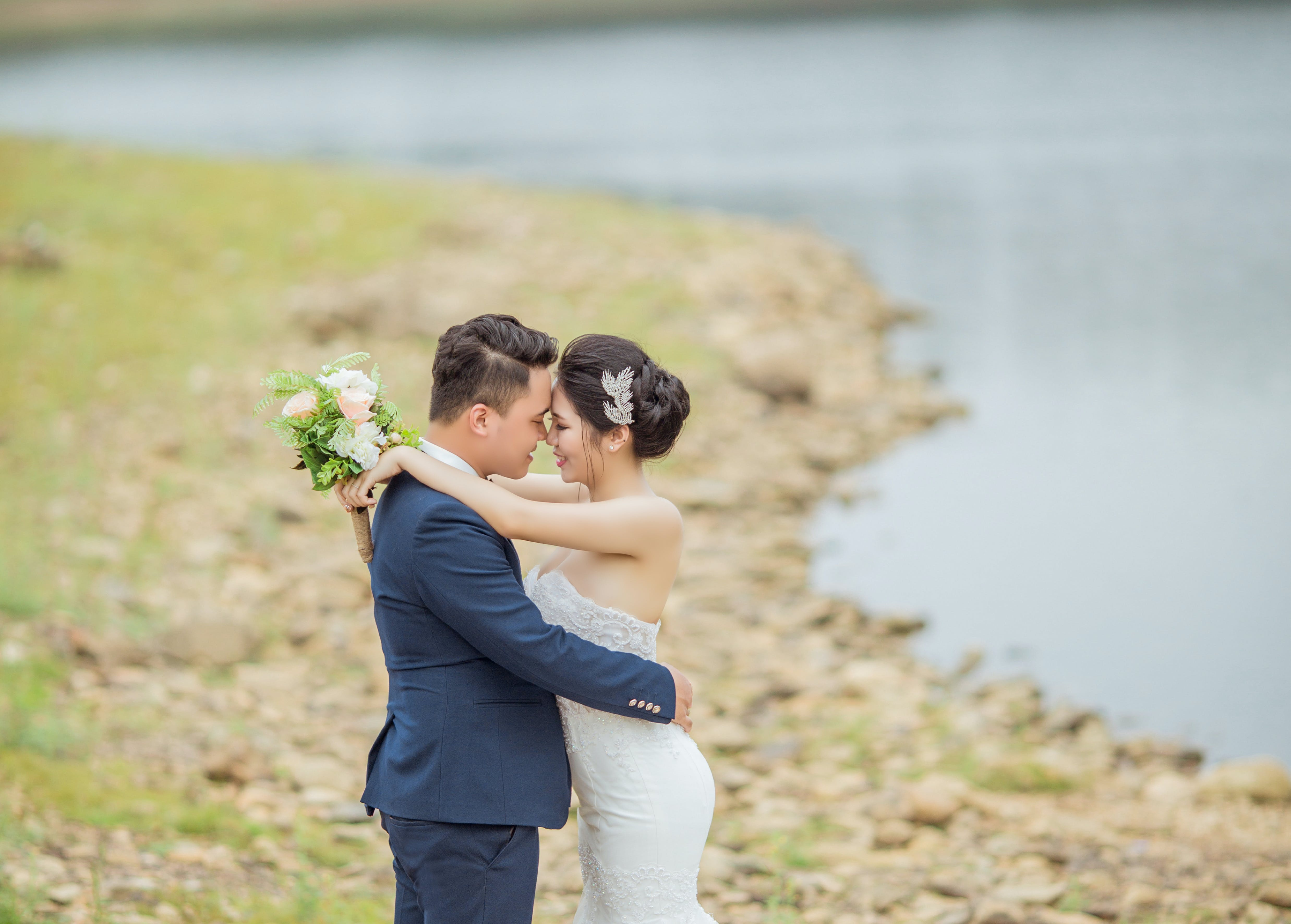 Newly Wed Coupe Standing Near Body of Water