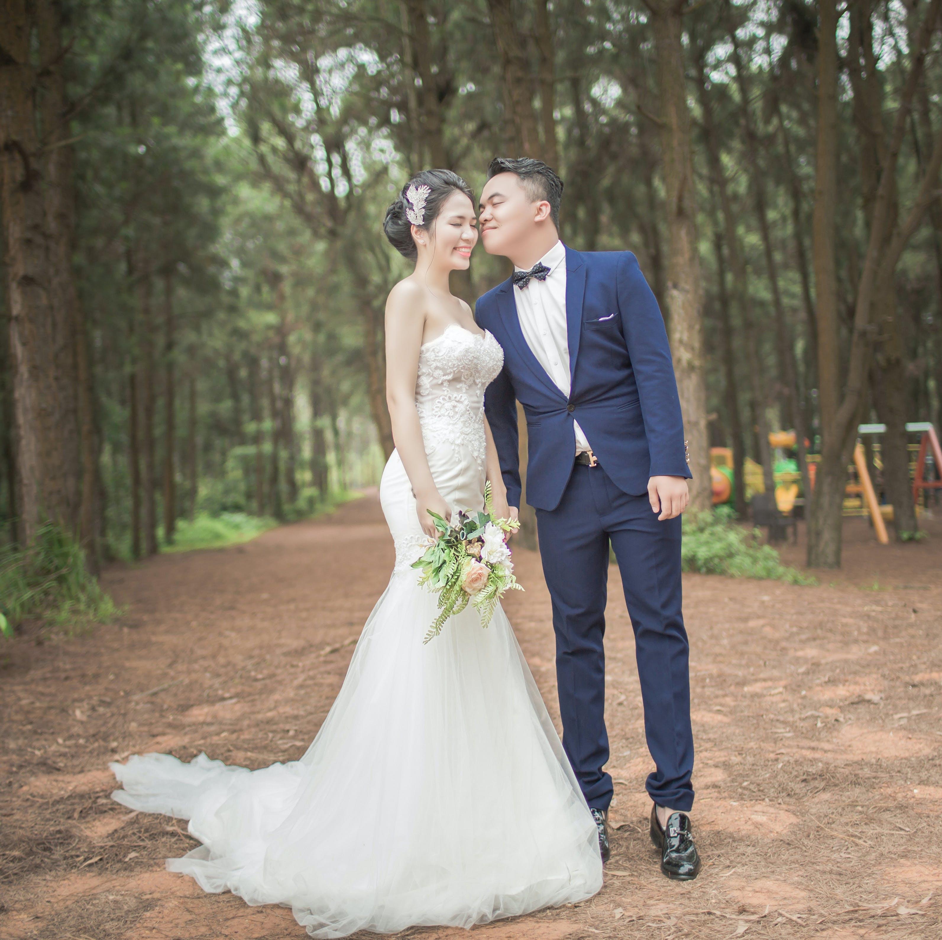 Bride and Groom Standing Between Trees