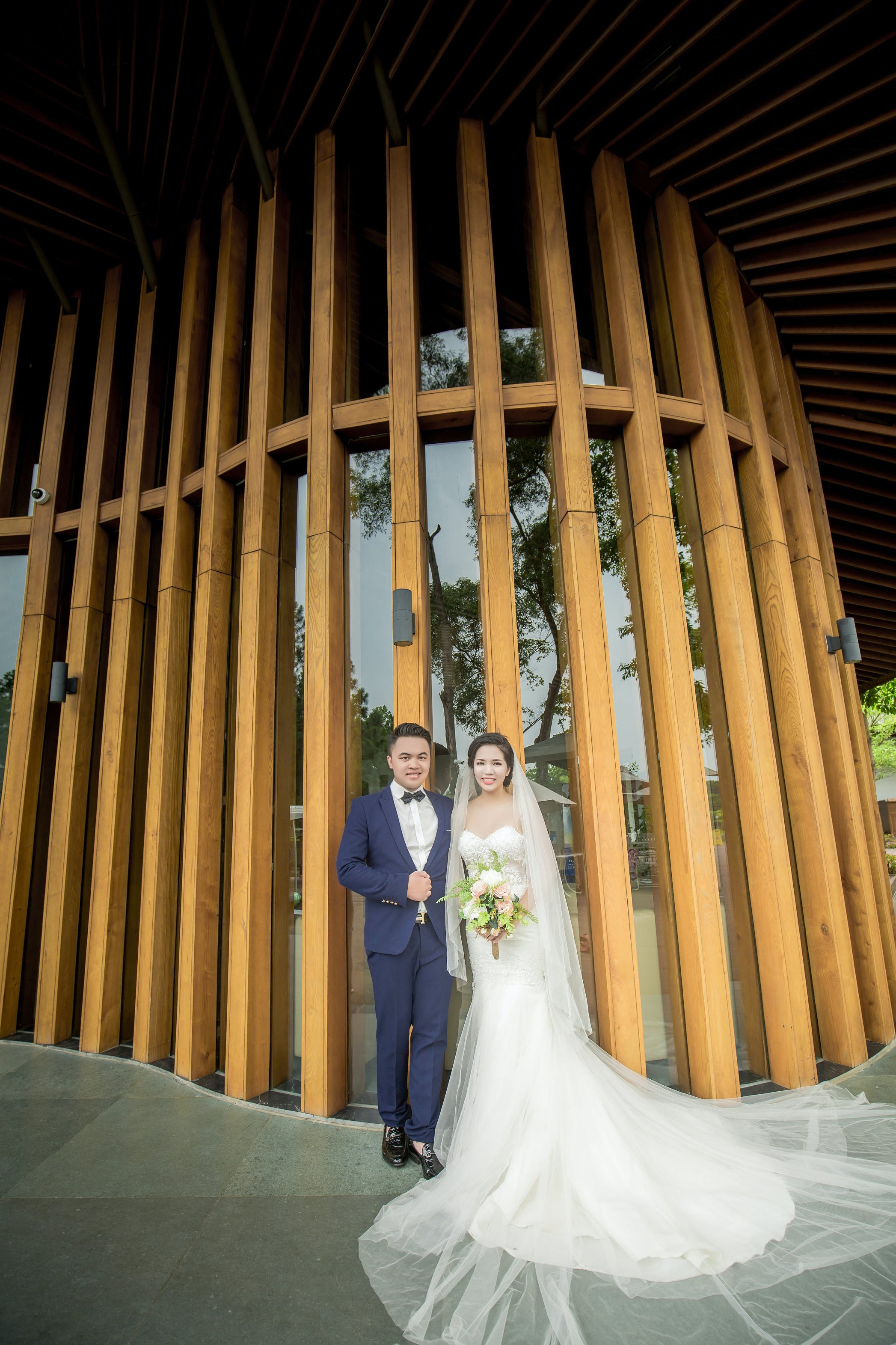 Photography of Couple Stands in Front Wooden Wall