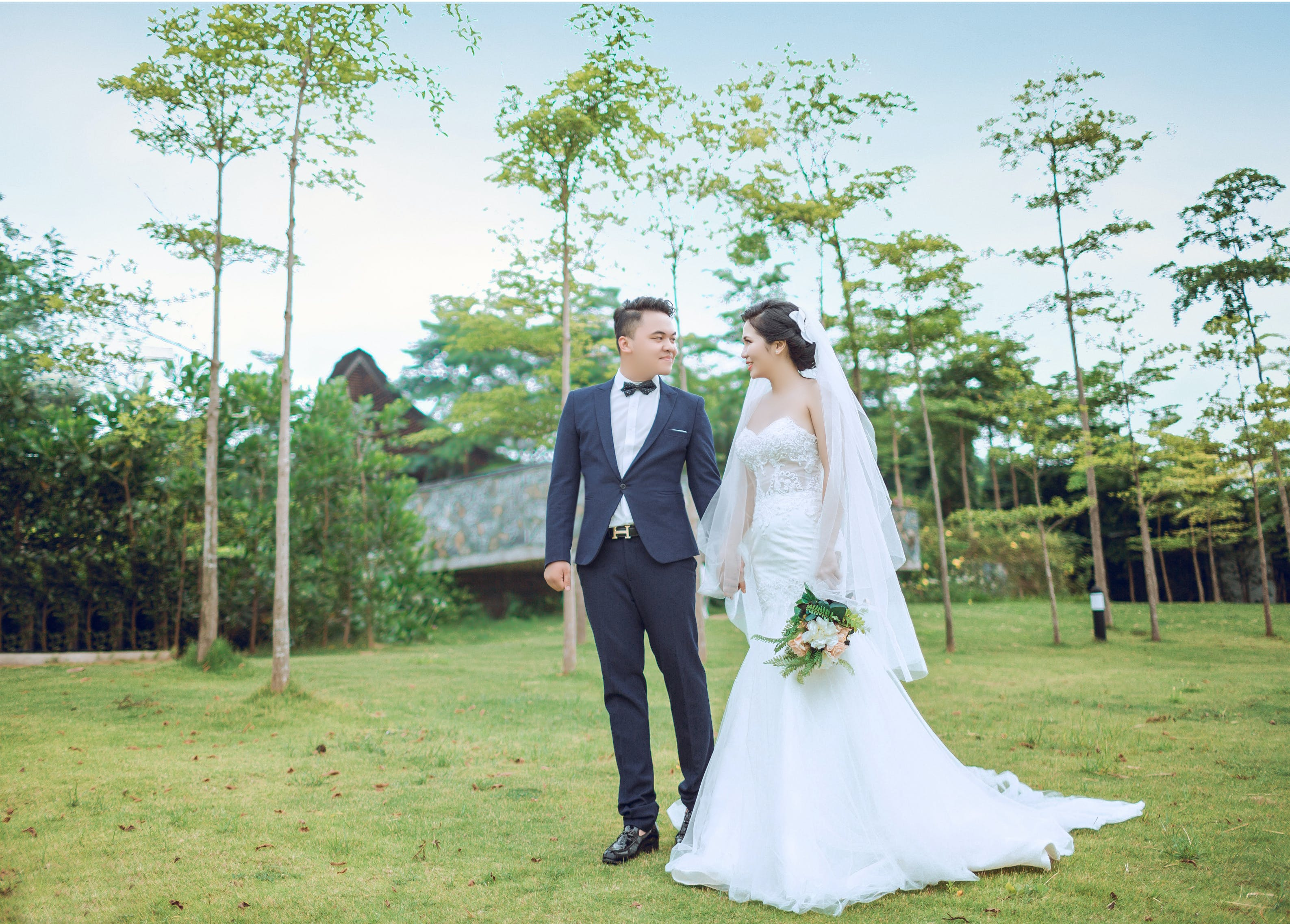 Bride and Groom Standing on Green Grass Surrounded by Green Leafed Trees