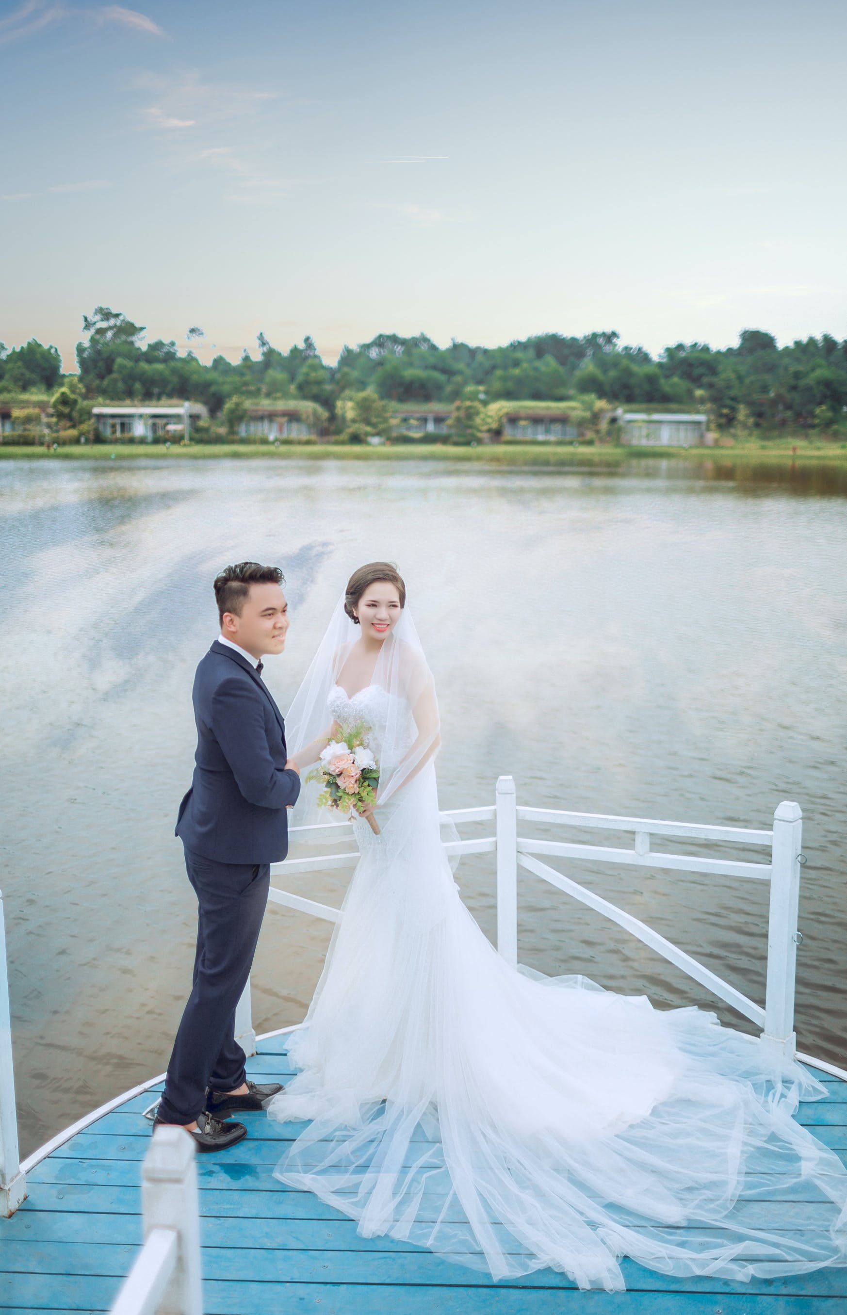 Just Married Man and Woman on Blue Platform Near Body of Water