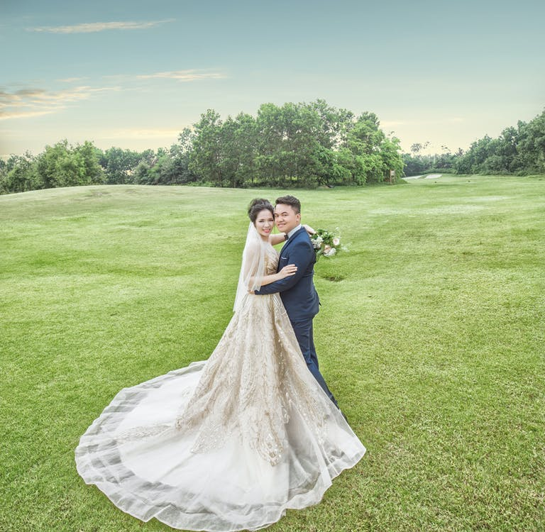 Bride and Groom Standing on Green Grass Field