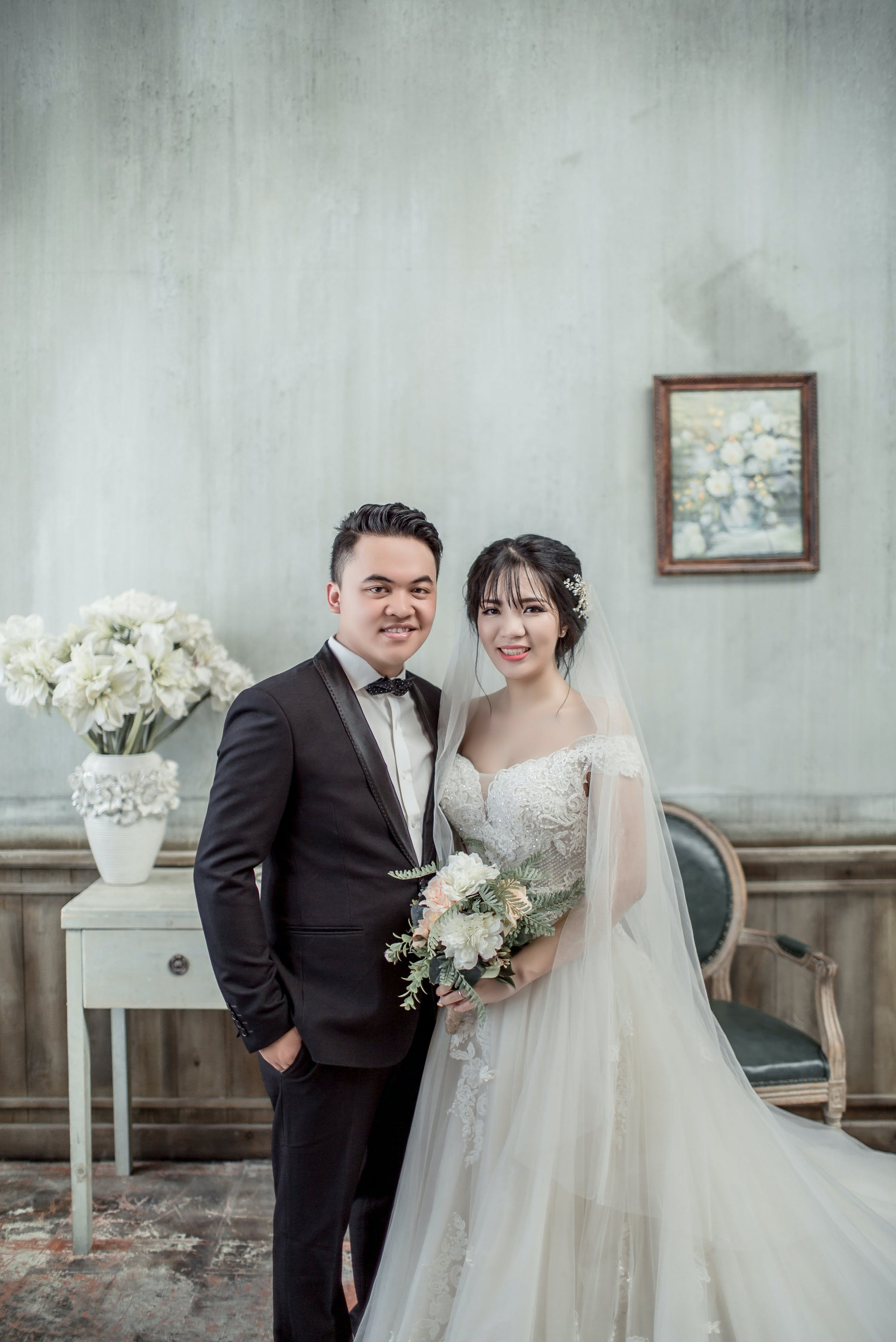 Man and Woman Taking Wedding Photo Inside Gray Concrete House With Wall Arts and Flowers on Vase