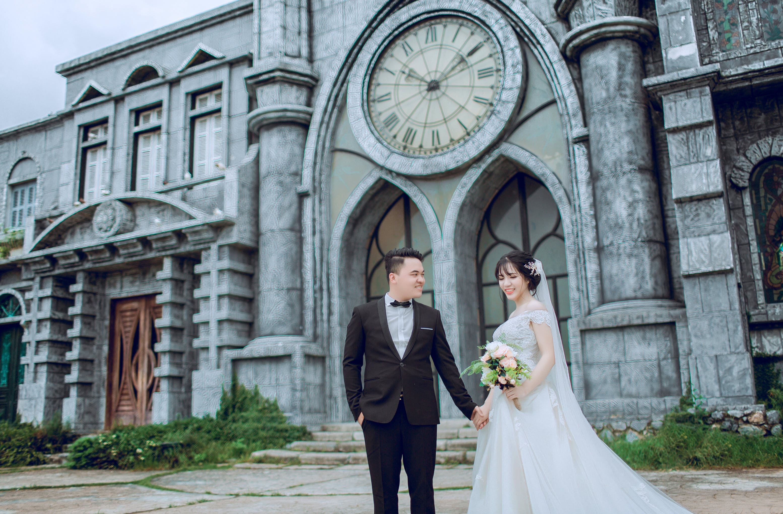 Groom Holding Bride's Hand Walking Near Cathedral