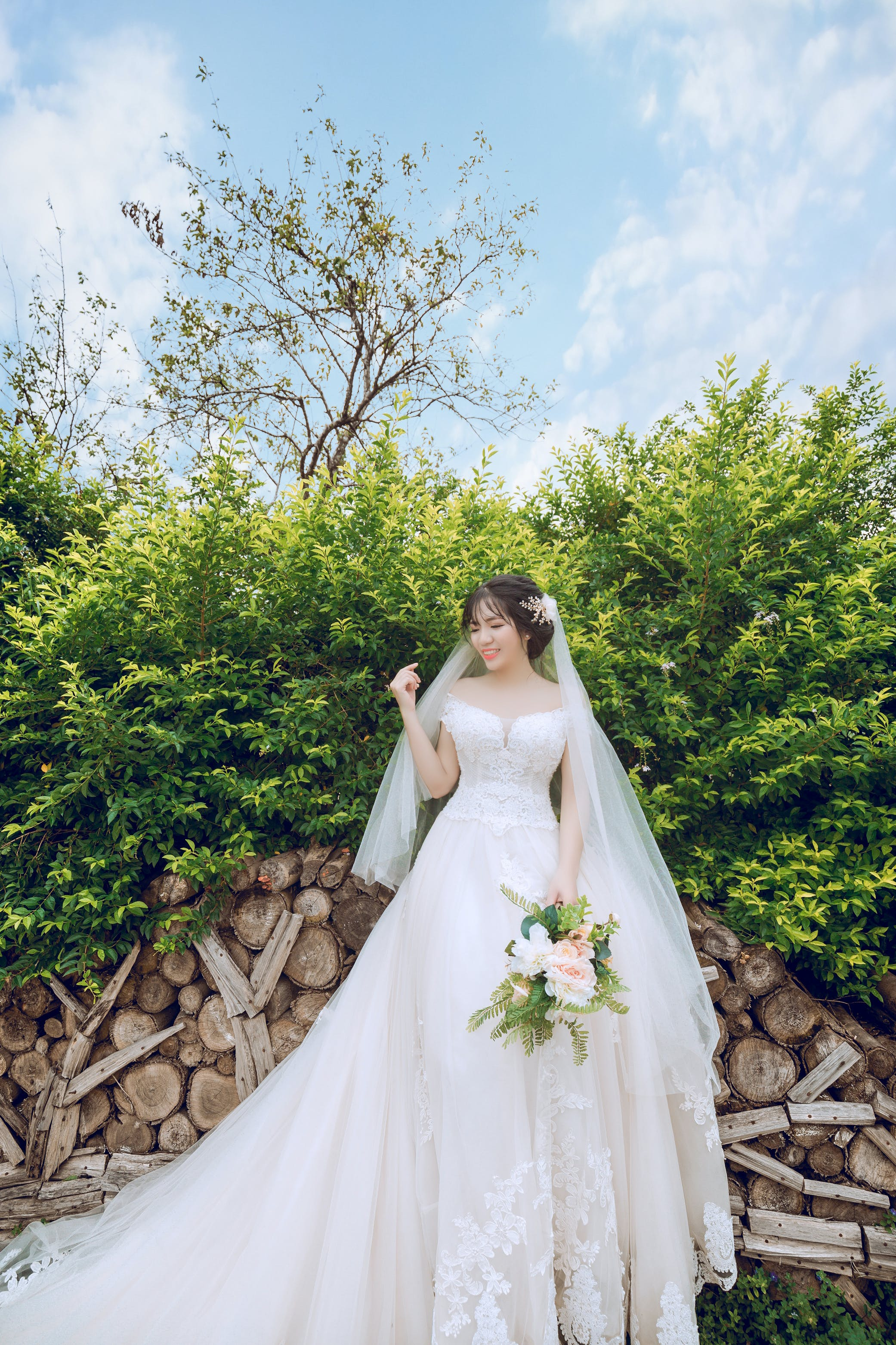 Bride Standing in Front Green Leaf Plant While Holding Bouquet