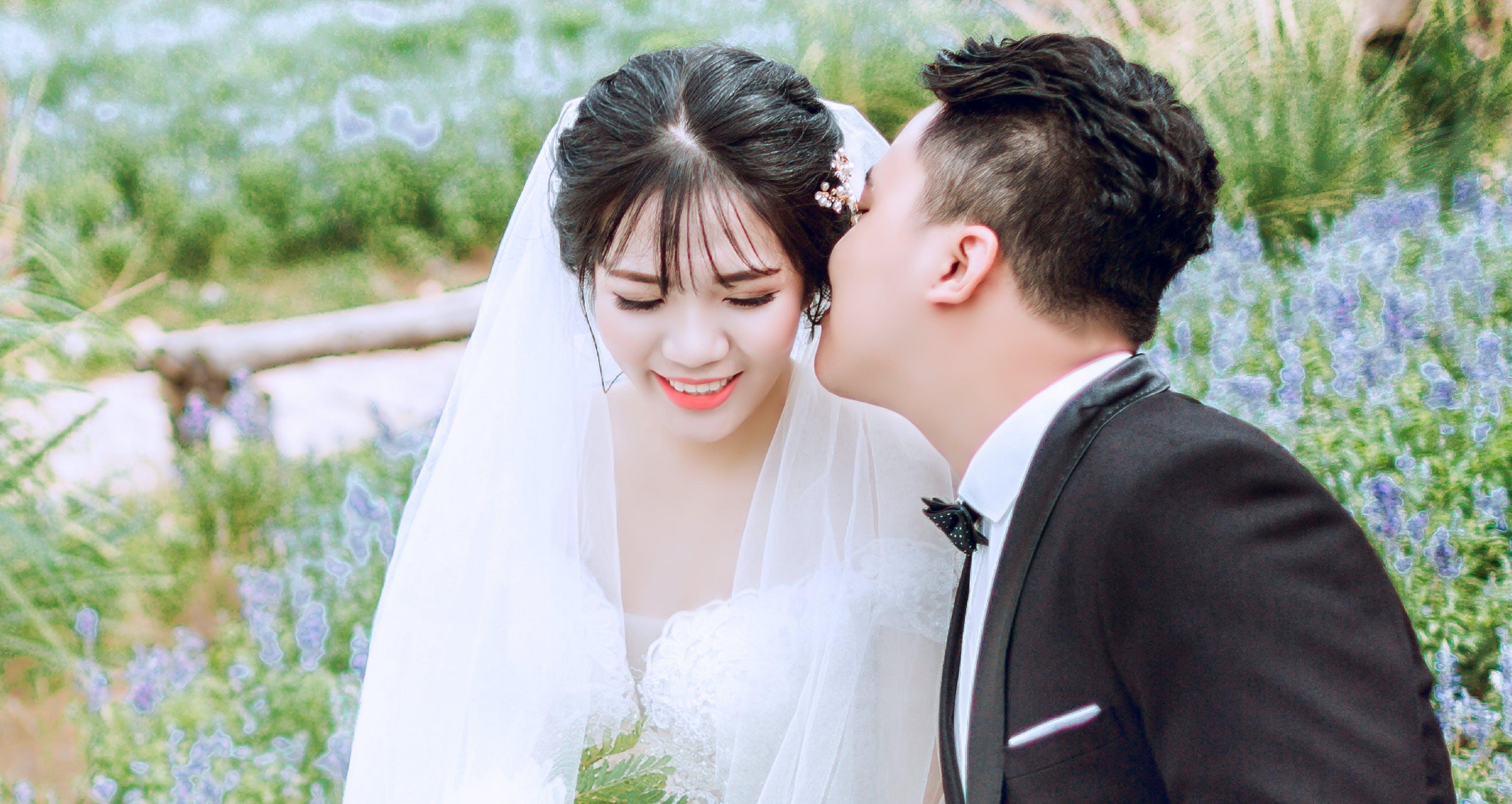 Groom Kissing Bride on Left Cheek