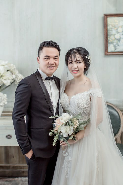 Man Wearing Black Suit Beside Woman Wearing Wedding Dress Standing Inside Room