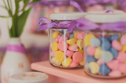 Photos gratuites de arrière-plan flou, bocal en verre, bonbons, couleurs