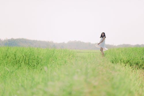Woman in White Dress on Green Grass Field