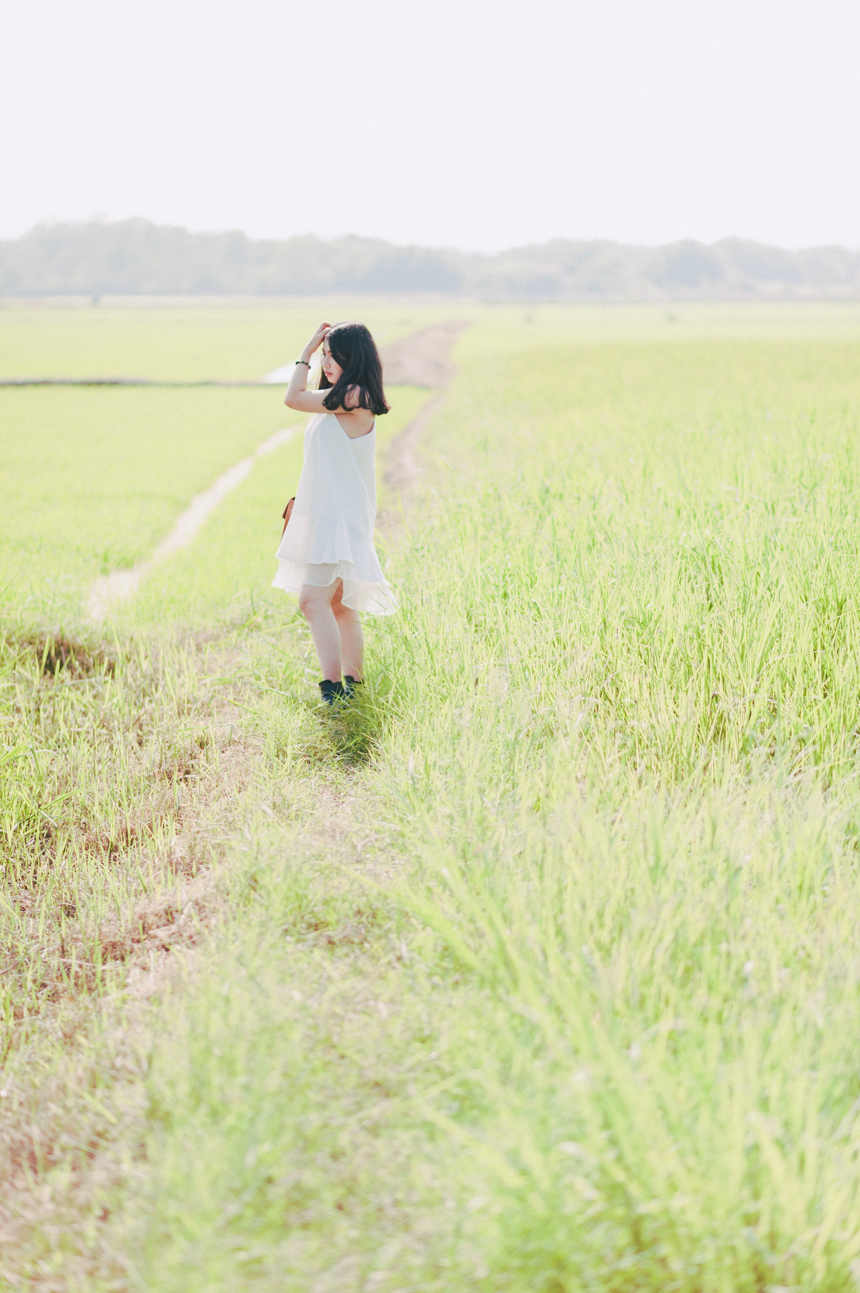 Woman Standing on Green Grass Field