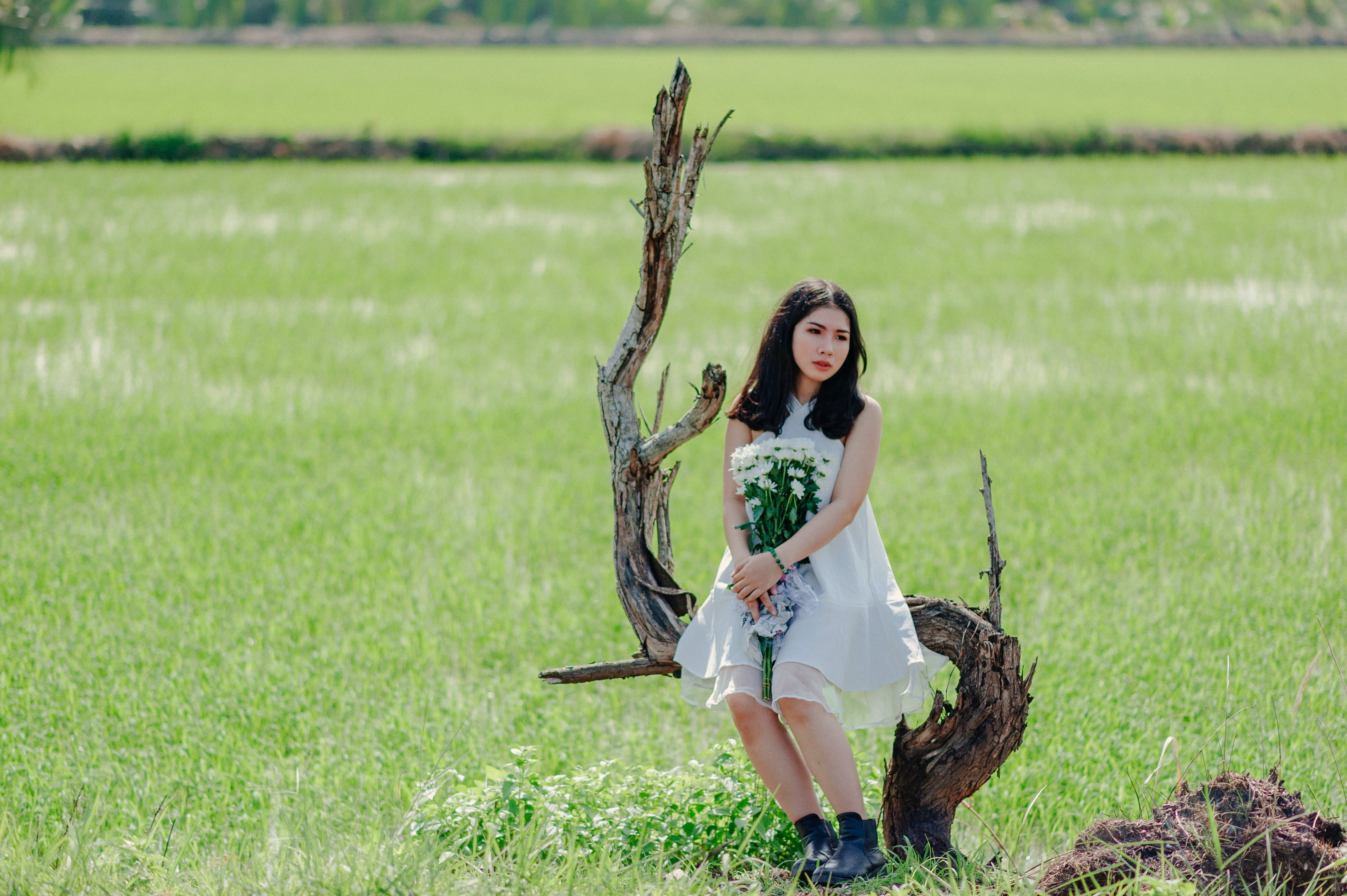 Woman Holding Bouquet of White Flower Sitting on Drift Wood