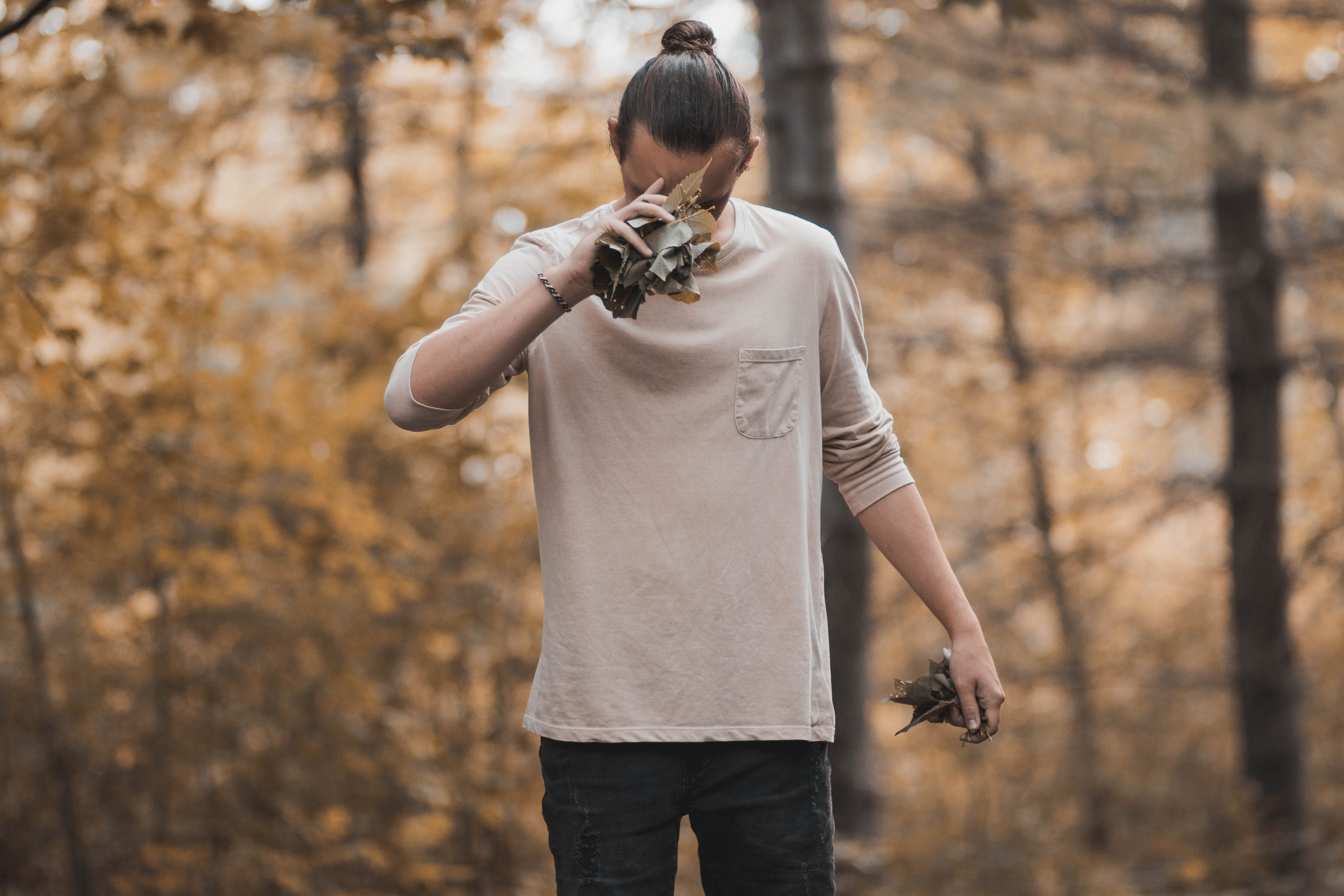 Man Holding Dried Leaves at the Forest