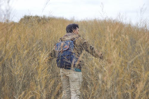 Man Carrying Backpack Walking on Grass Field
