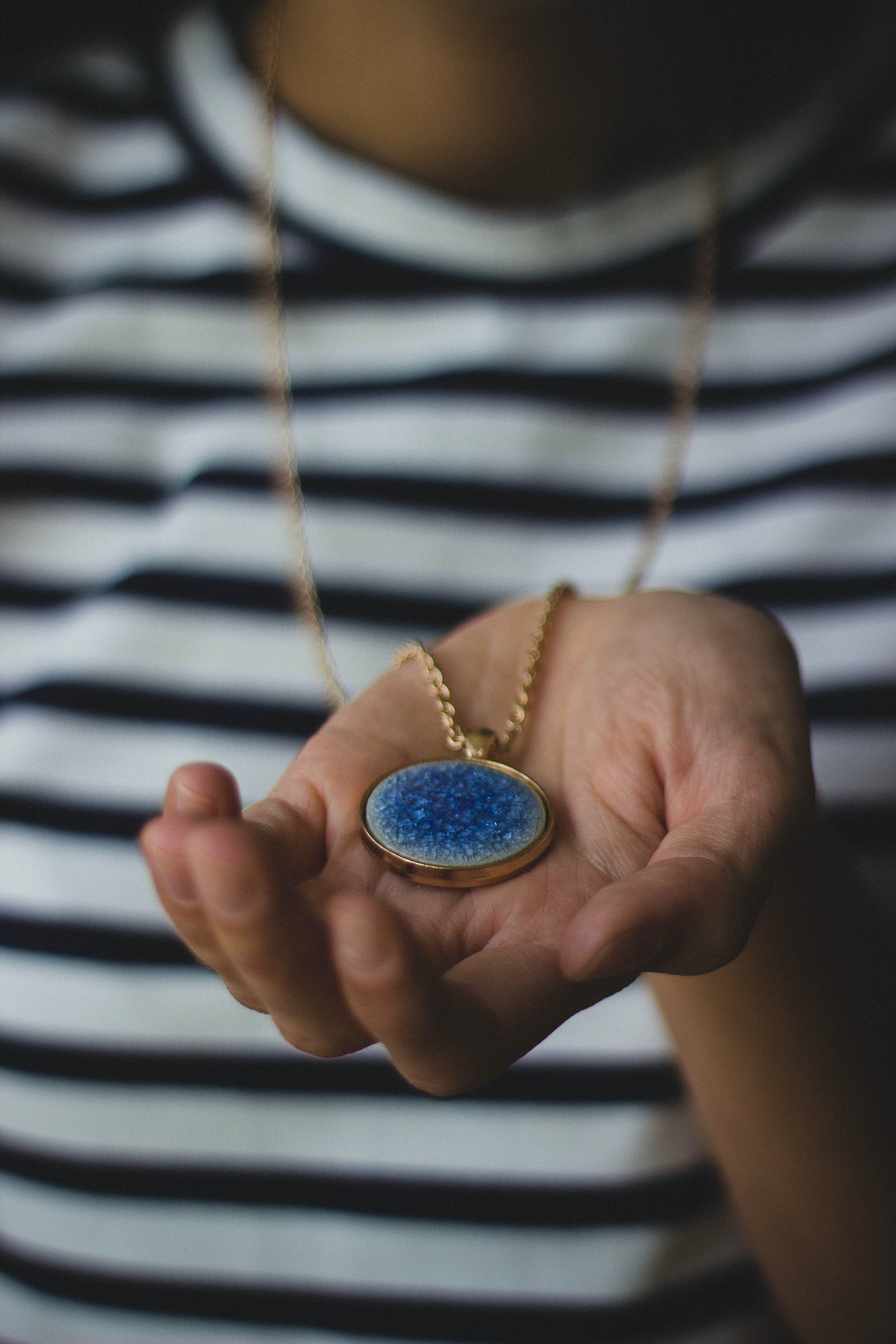 Person Holding Gold-colored Pendant