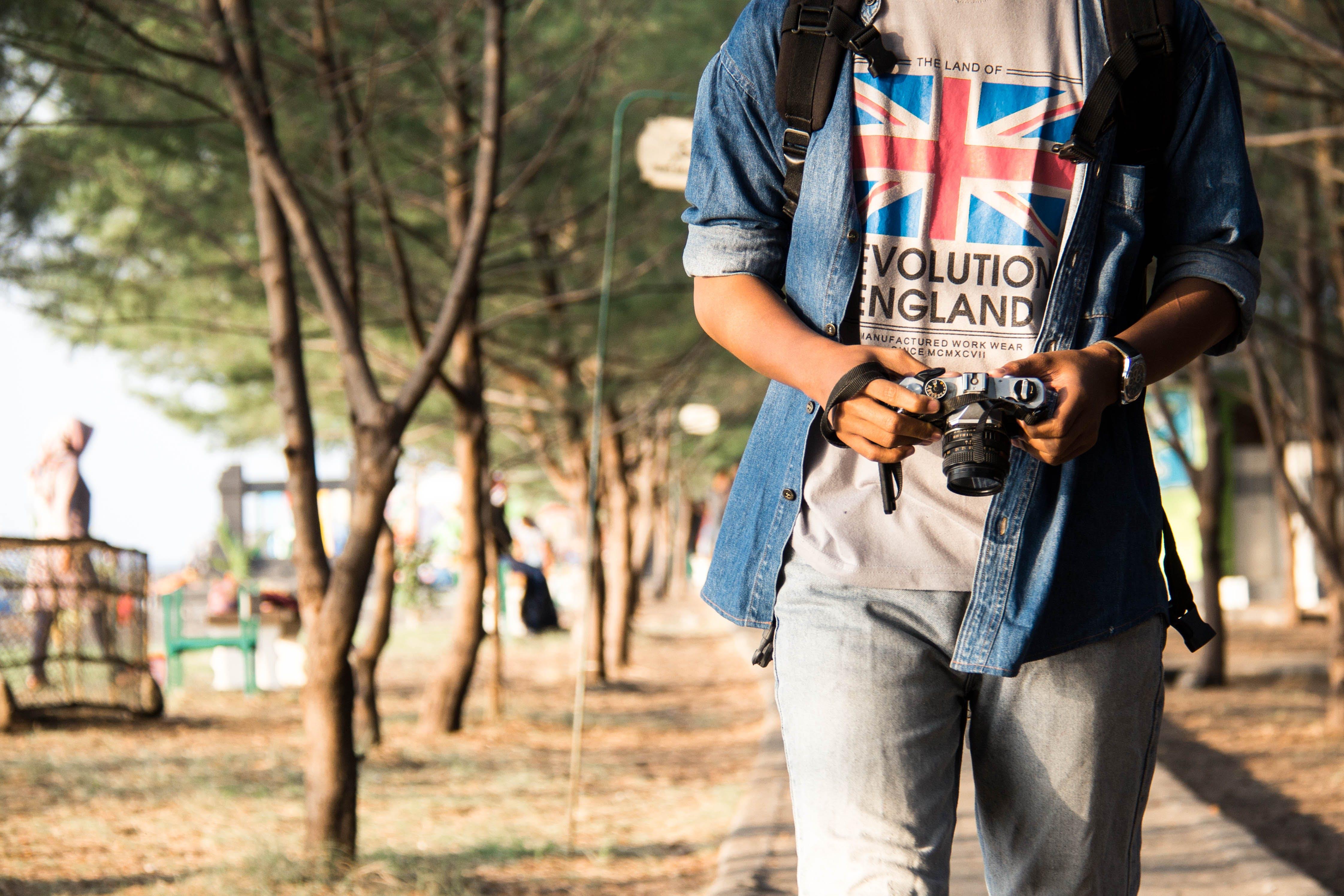 Man Holding Dslr Camera While Walking
