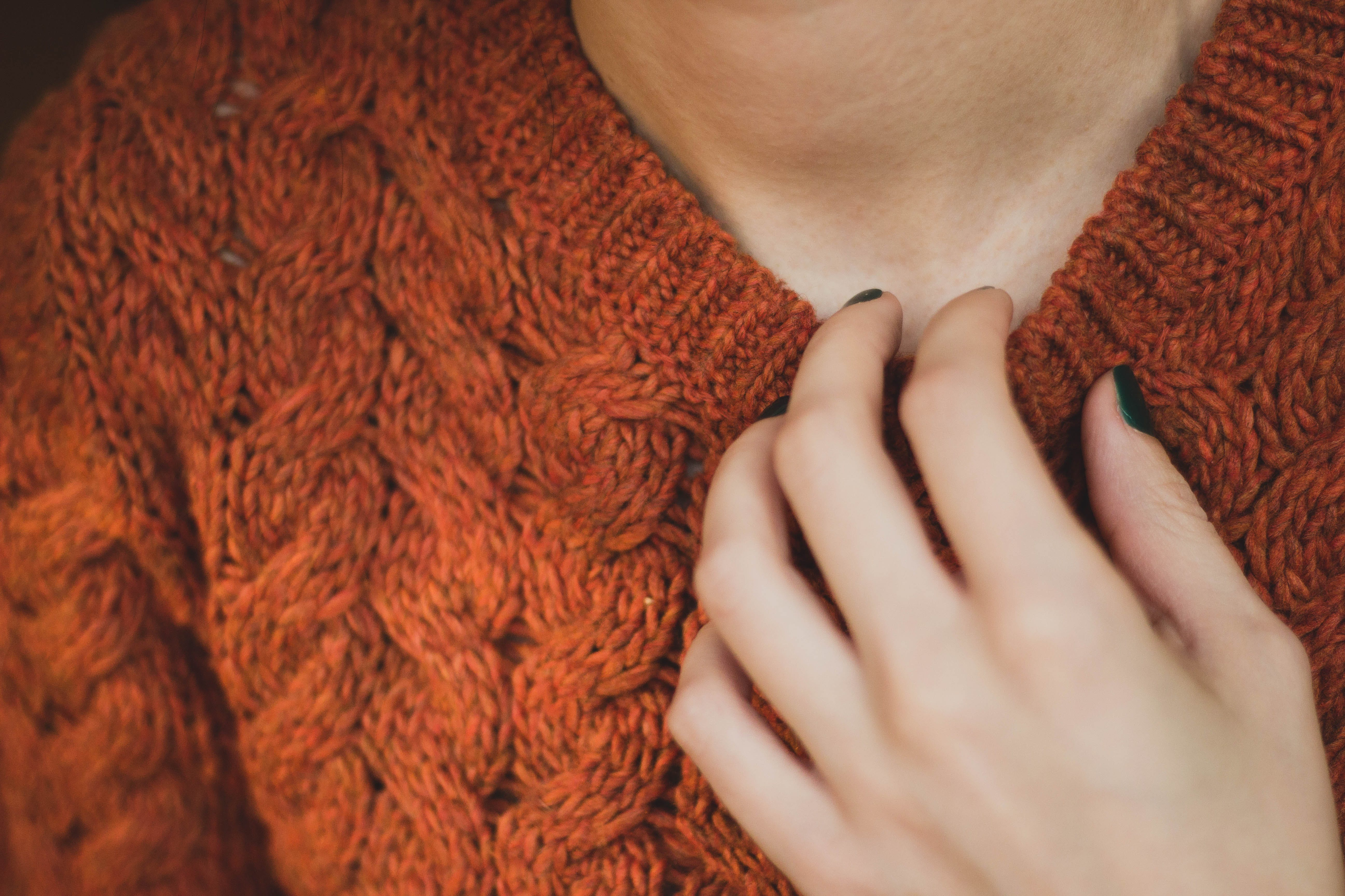 Person Holding on Brown Knitted Sweater