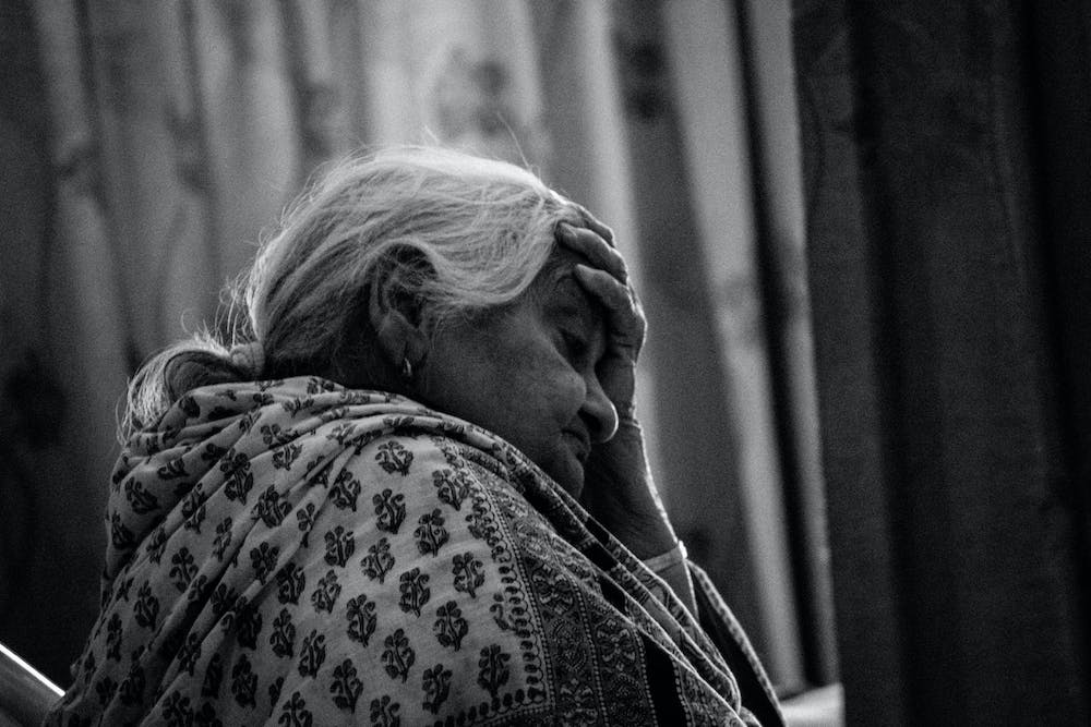 Old woman touching her forehead | Photo: Pexels