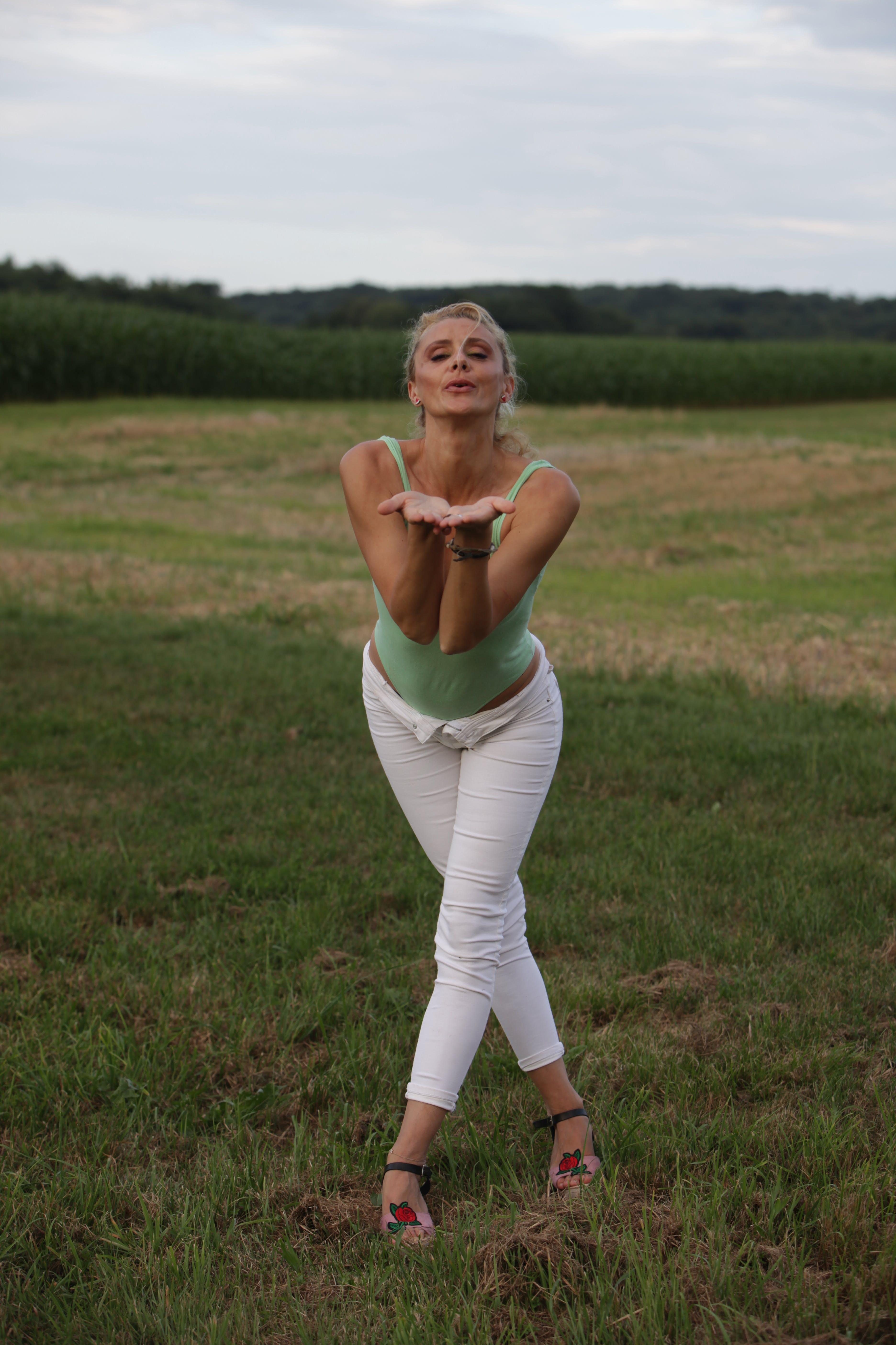 Woman Blowing While Standing on Green Grass