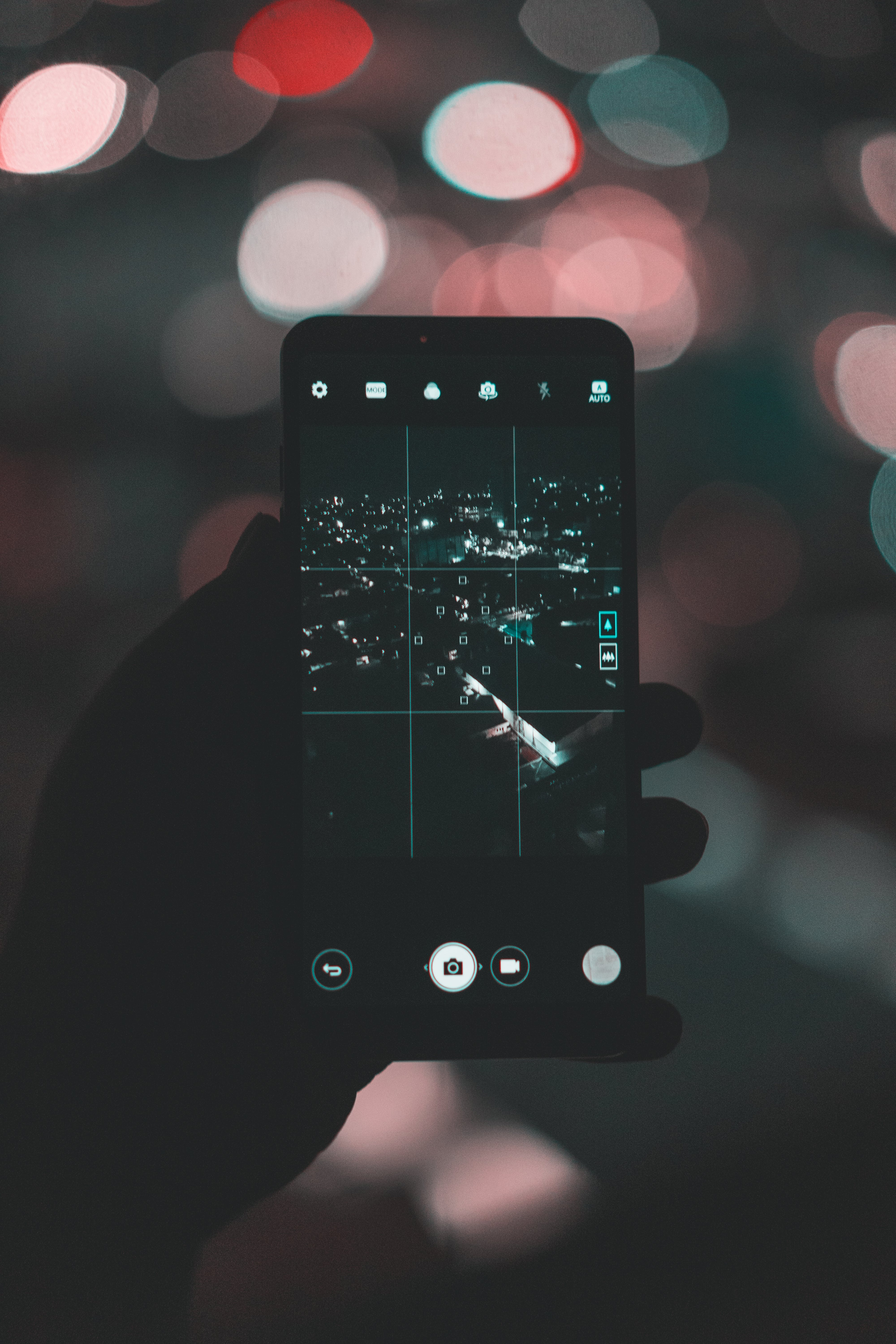 Photo of Person Taking Picture of City During Evening