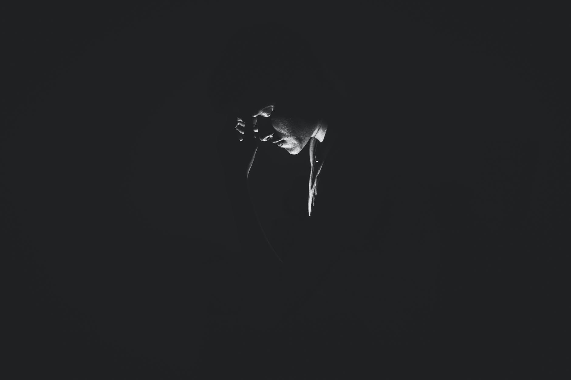 monochrome photography of person on dark room