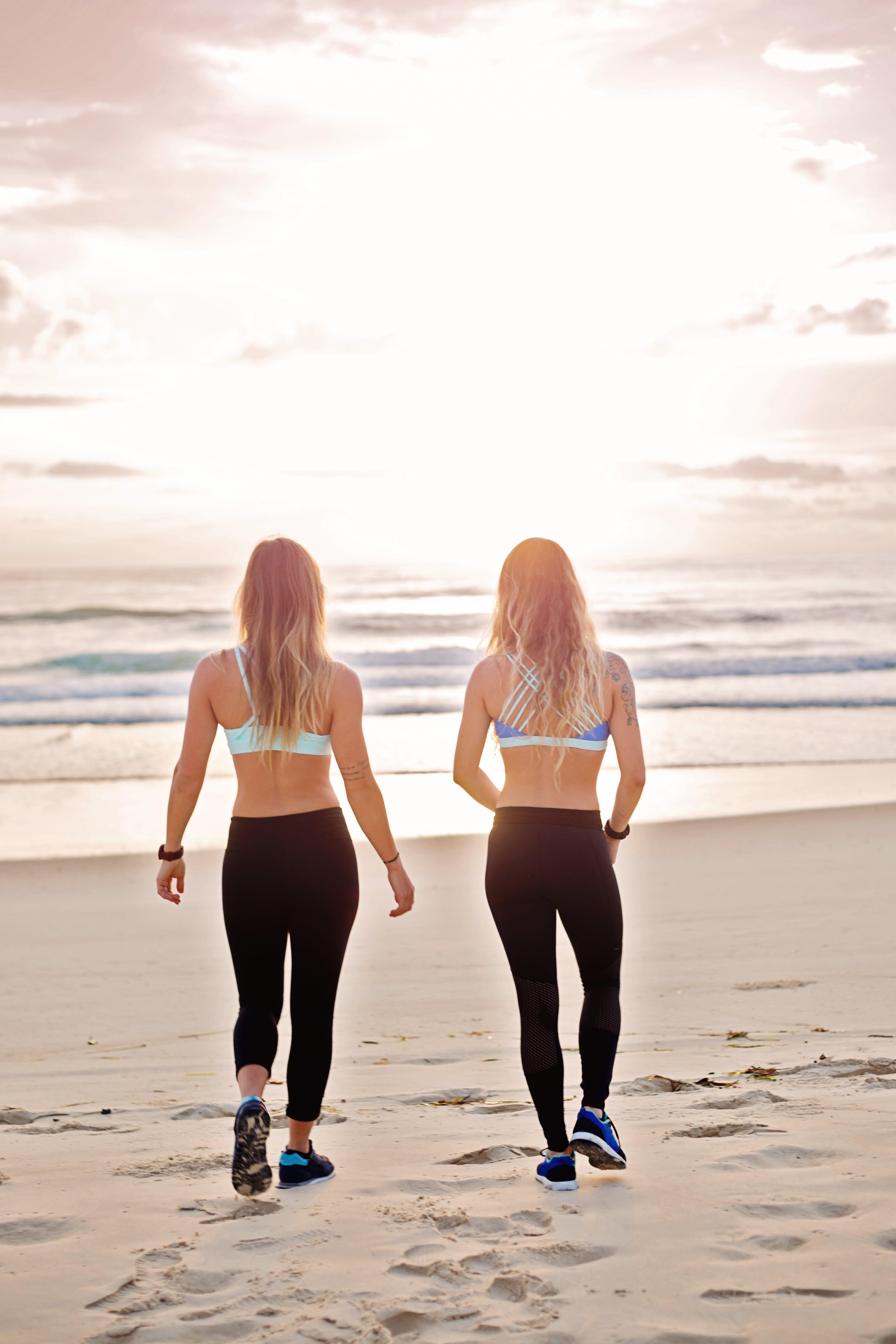 Two Women Walking on Seashore While Talking