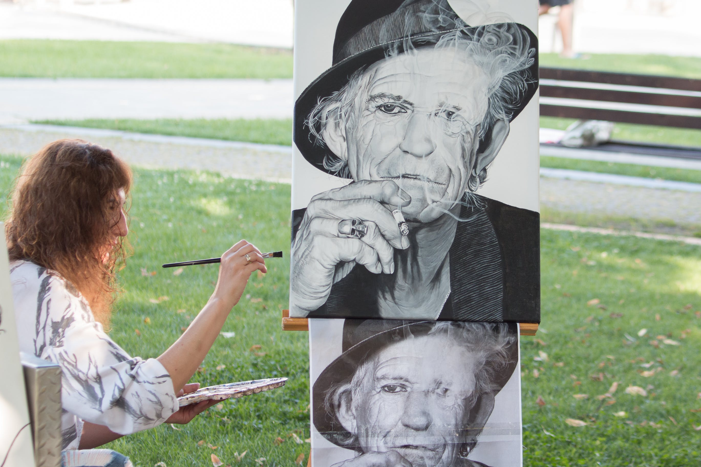 Person painting man's portrait from photograph outdoors