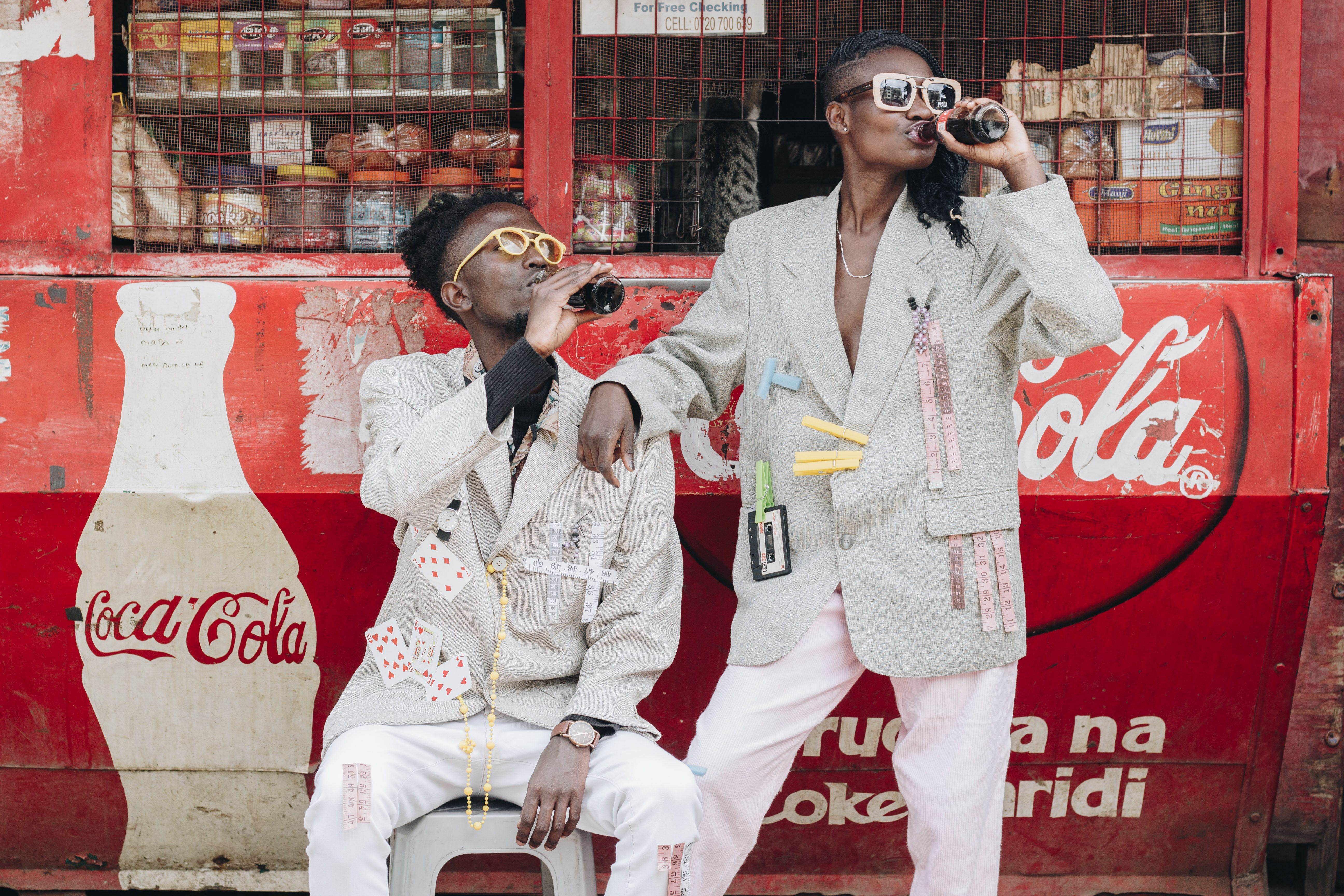 Two Person Drinking Coca-cola Next to a Kiosk