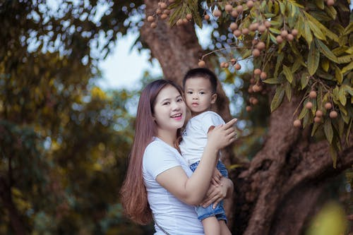 Woman Carrying Child Standing Near Tree